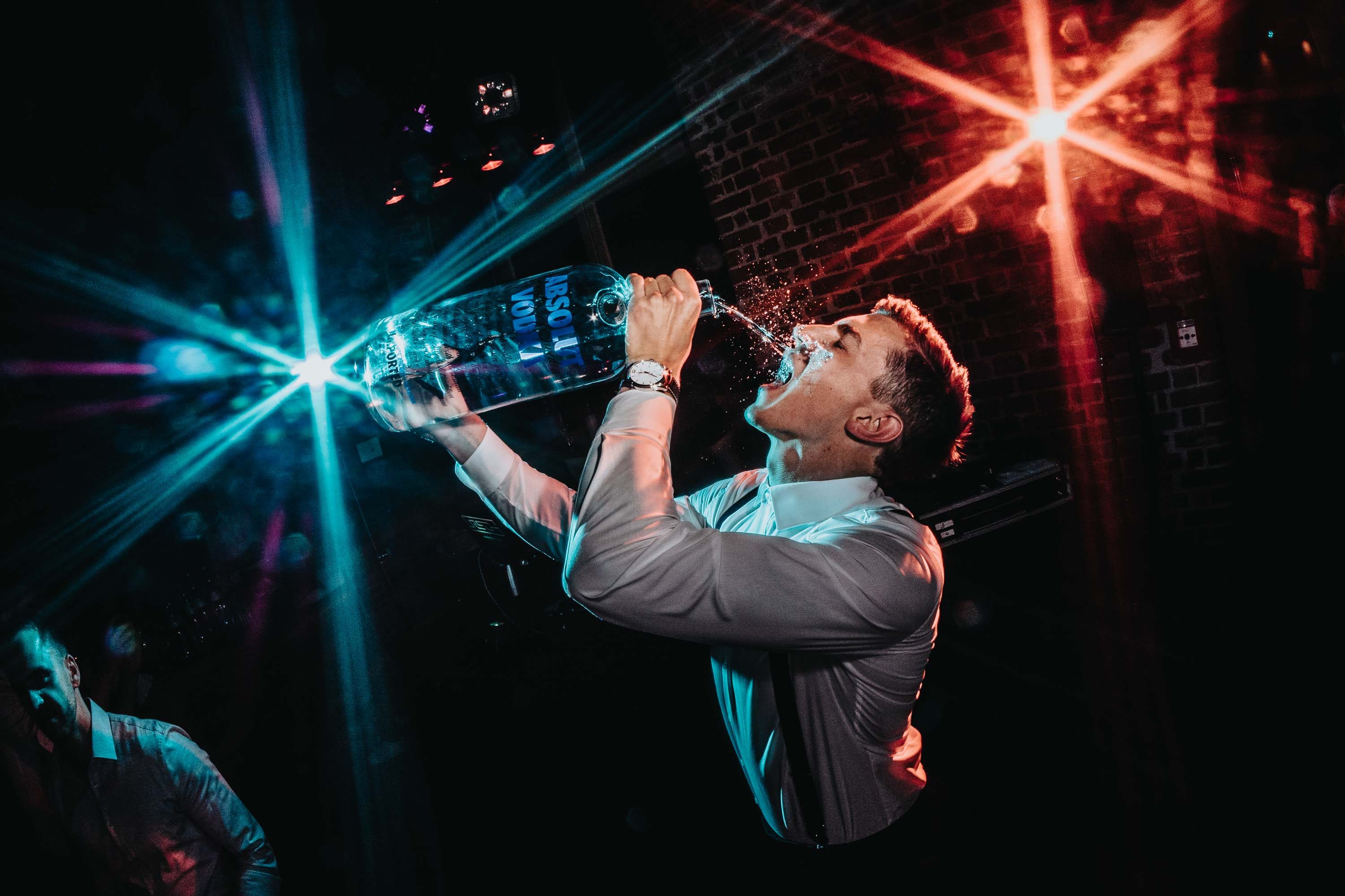 Guest drinks directly from gallon on Absolut Vodka,  photo by FineArt Weddings, Germany