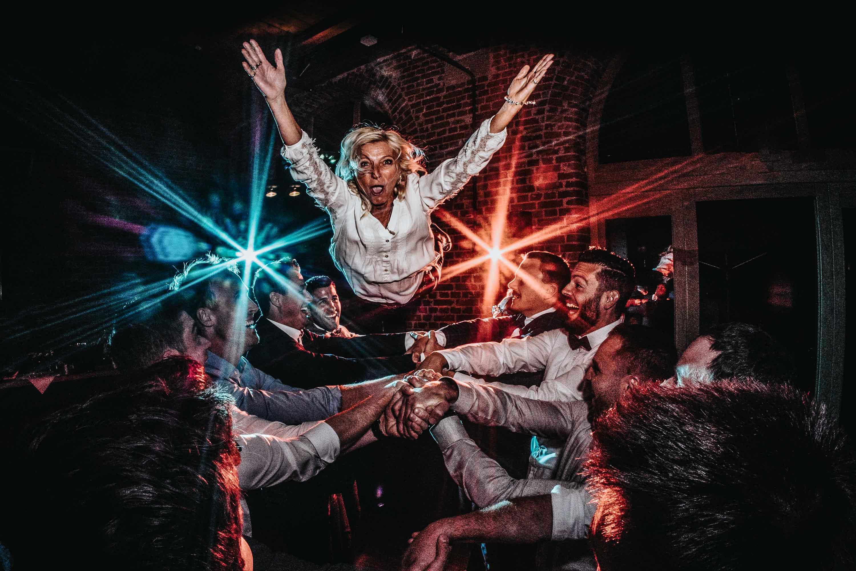Guest flies on top of groomsmen's arms - photo by FineArt Weddings, Germany