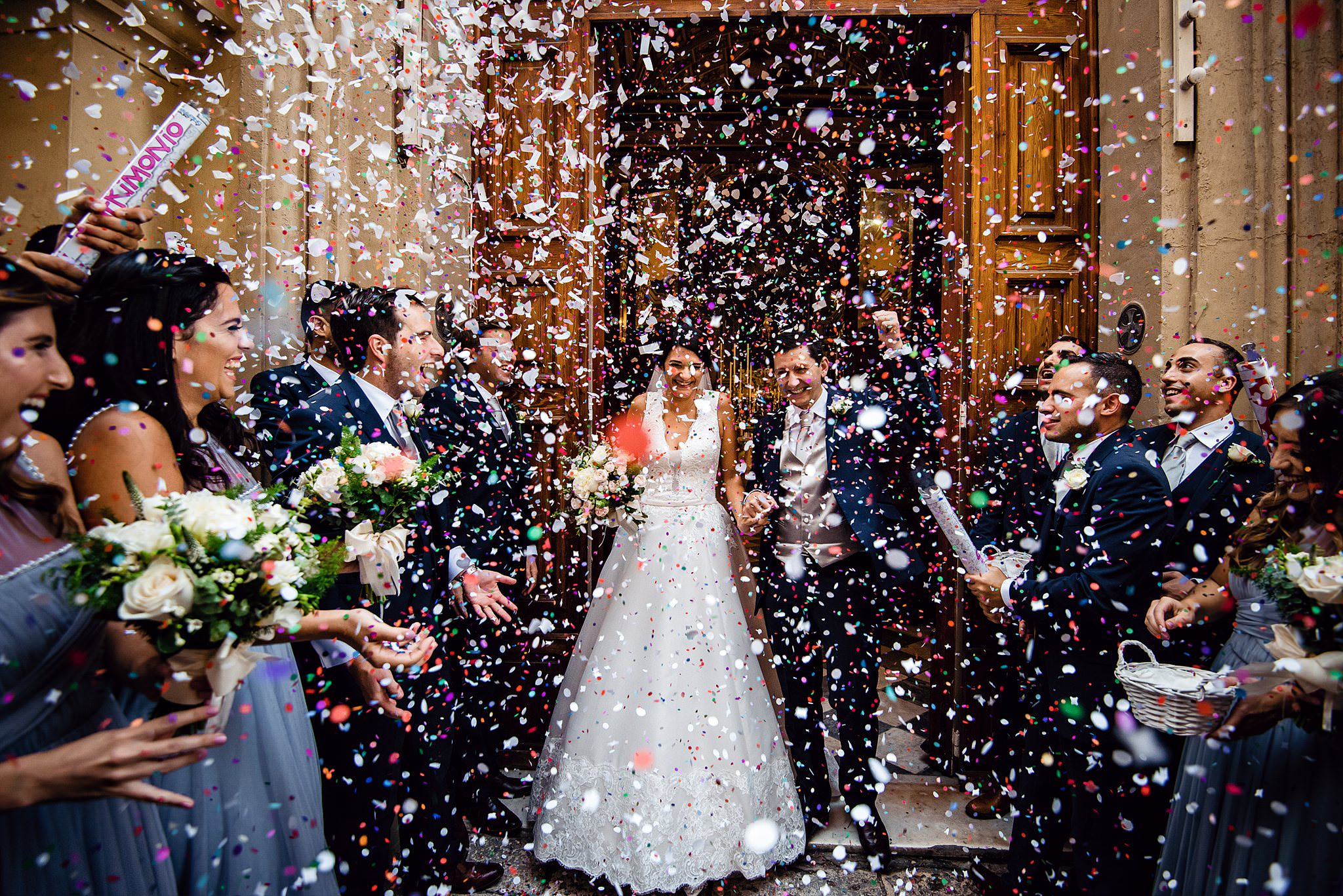 bride and groom exiting the church surrounded by confetti- photo by Shane P Watts Photography