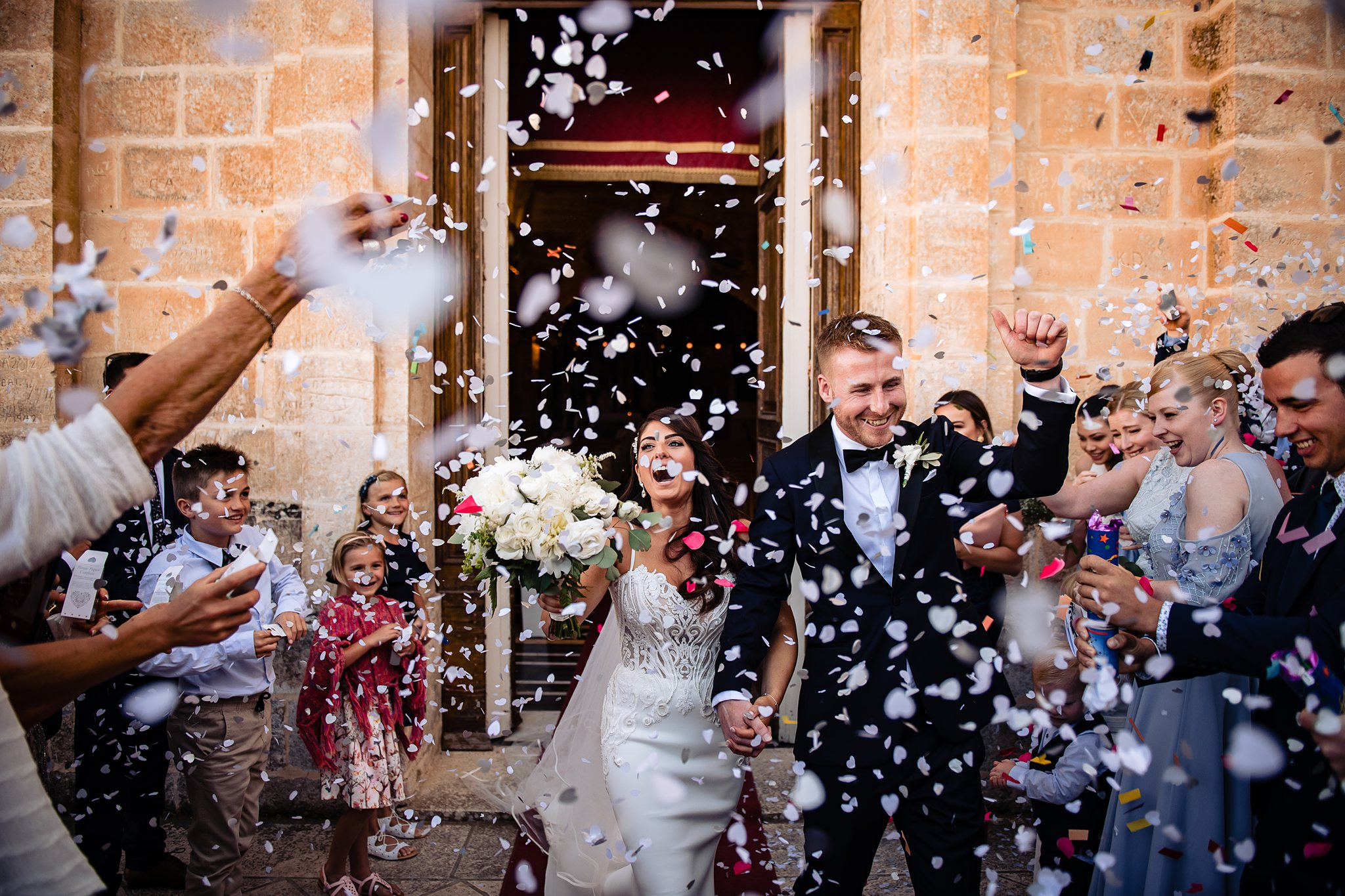 bride and groom exiting the church surrounded by flower petals and friends- photo by Shane P Watts Photography