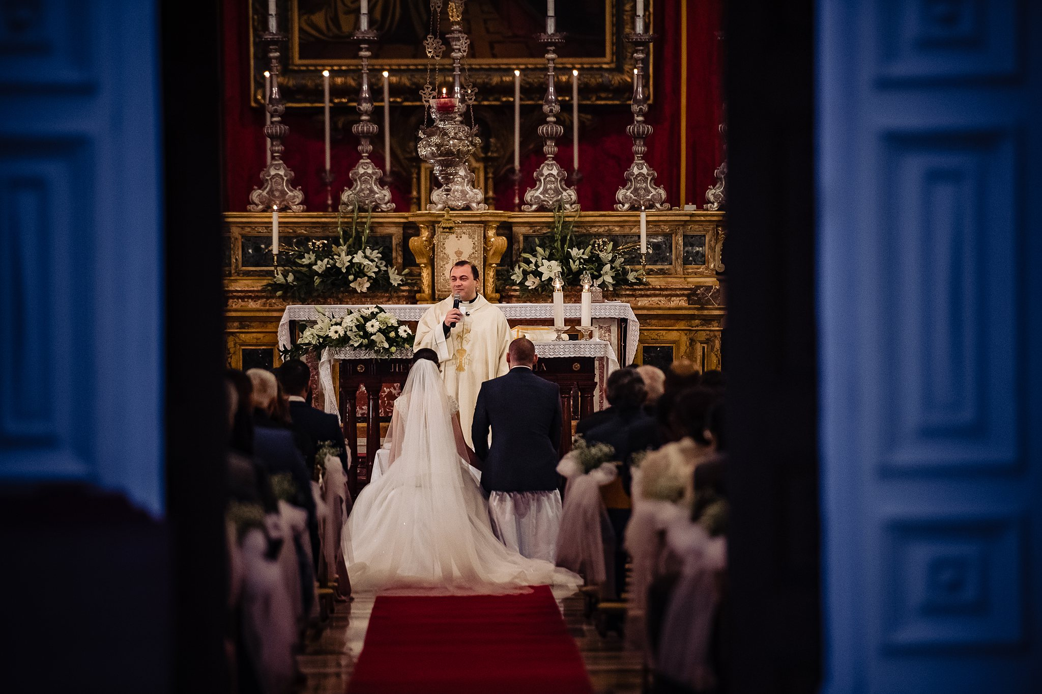 bride and groom kneeling during their ceremony in church- photo by Shane P Watts Photography