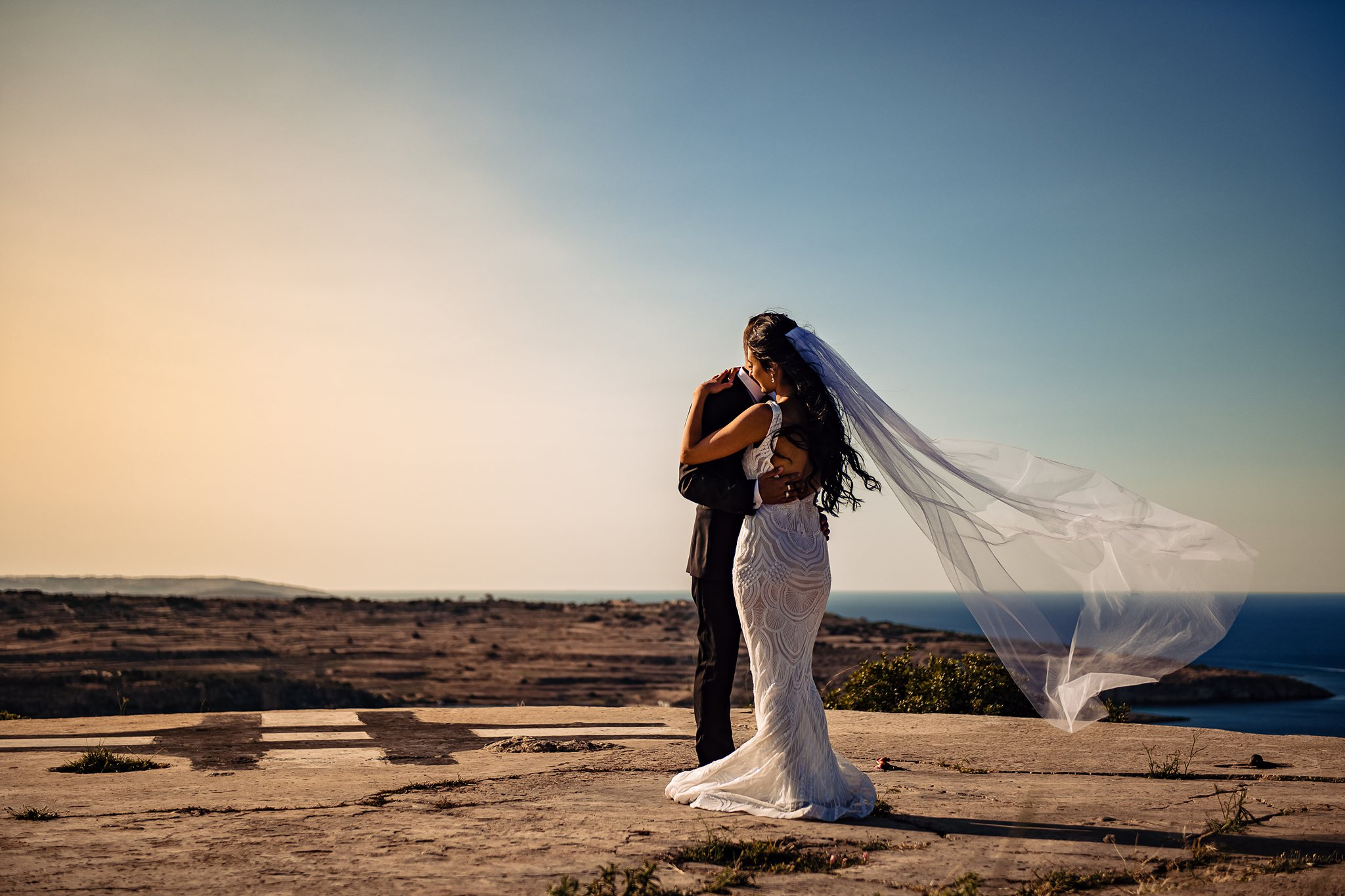 bride and groom portrait by the sea with her veil blowing in the wind- photo by Shane P Watts Photography
