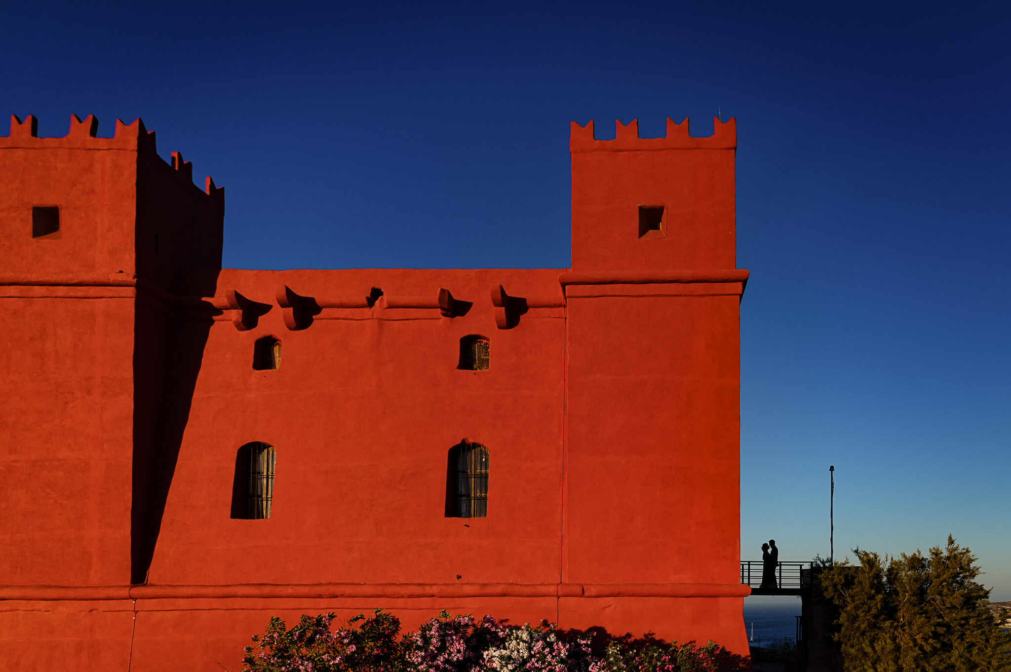 bride and groom silhouette portrait by a red castle- photo by Shane P Watts Photography