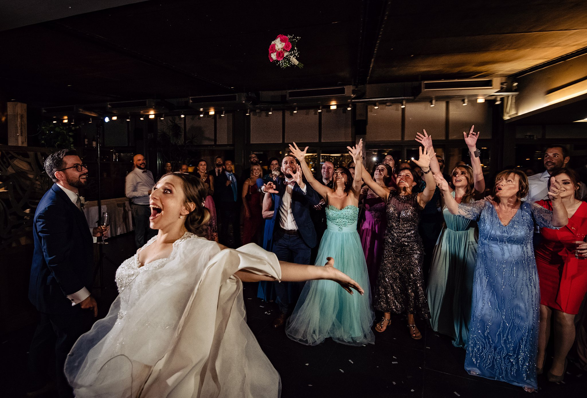 bride excitingly tossing the bouquet to the single women- photo by Shane P Watts Photography