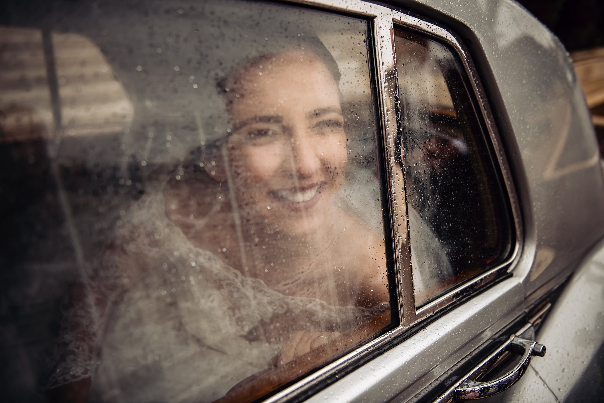 bride looking out the rain drop window of car with excitement- photo by Shane P Watts Photography