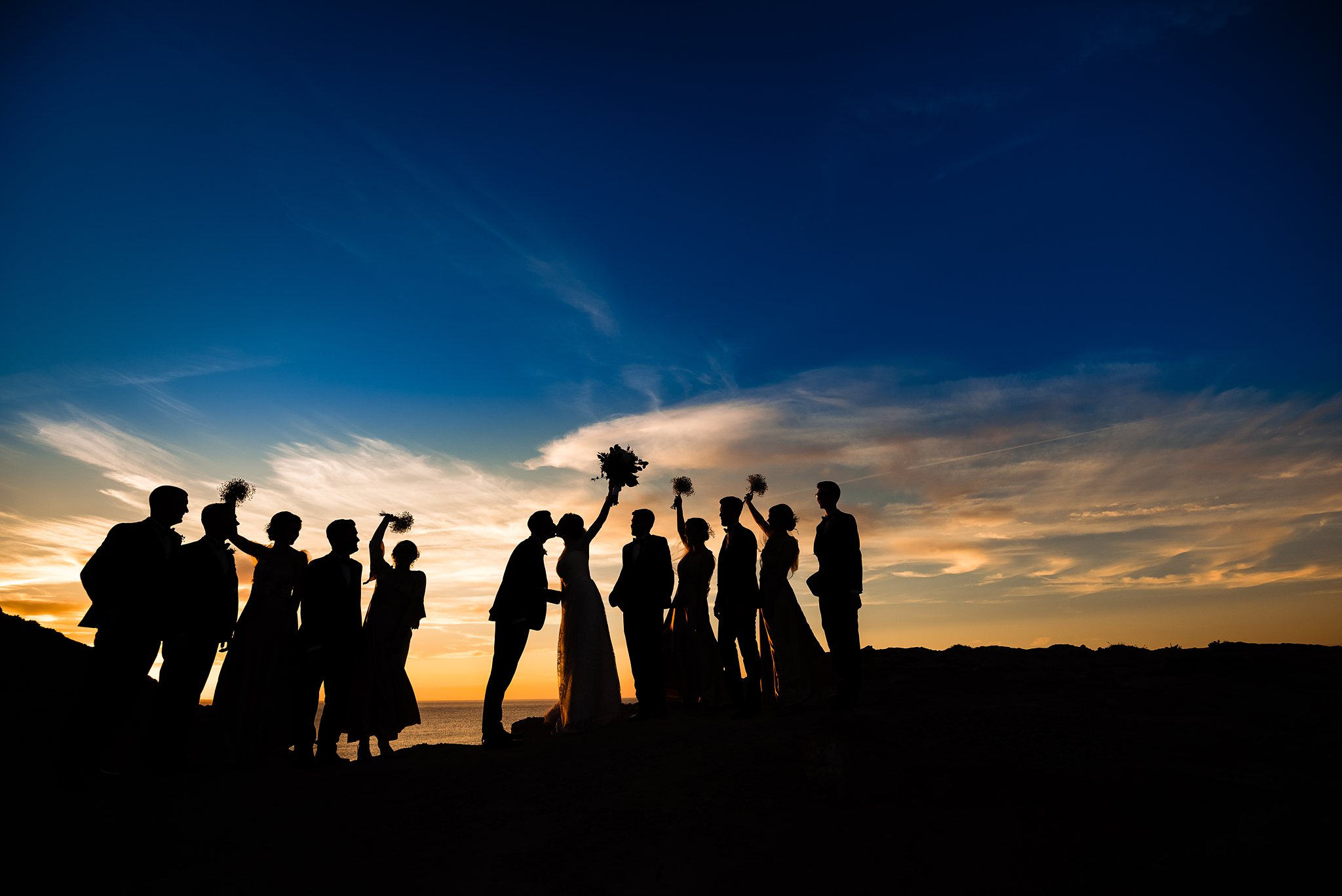 Silhouette of bridal party against sunset - photo by Shane P. Watts Photography