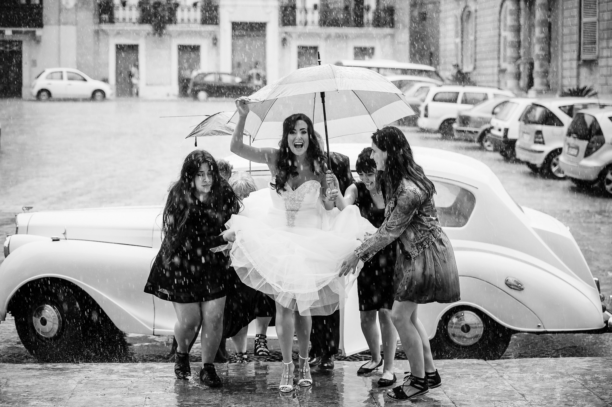 Rainy day bride ascending stairs with help from her friends- photo by Shane P. Watts Photography
