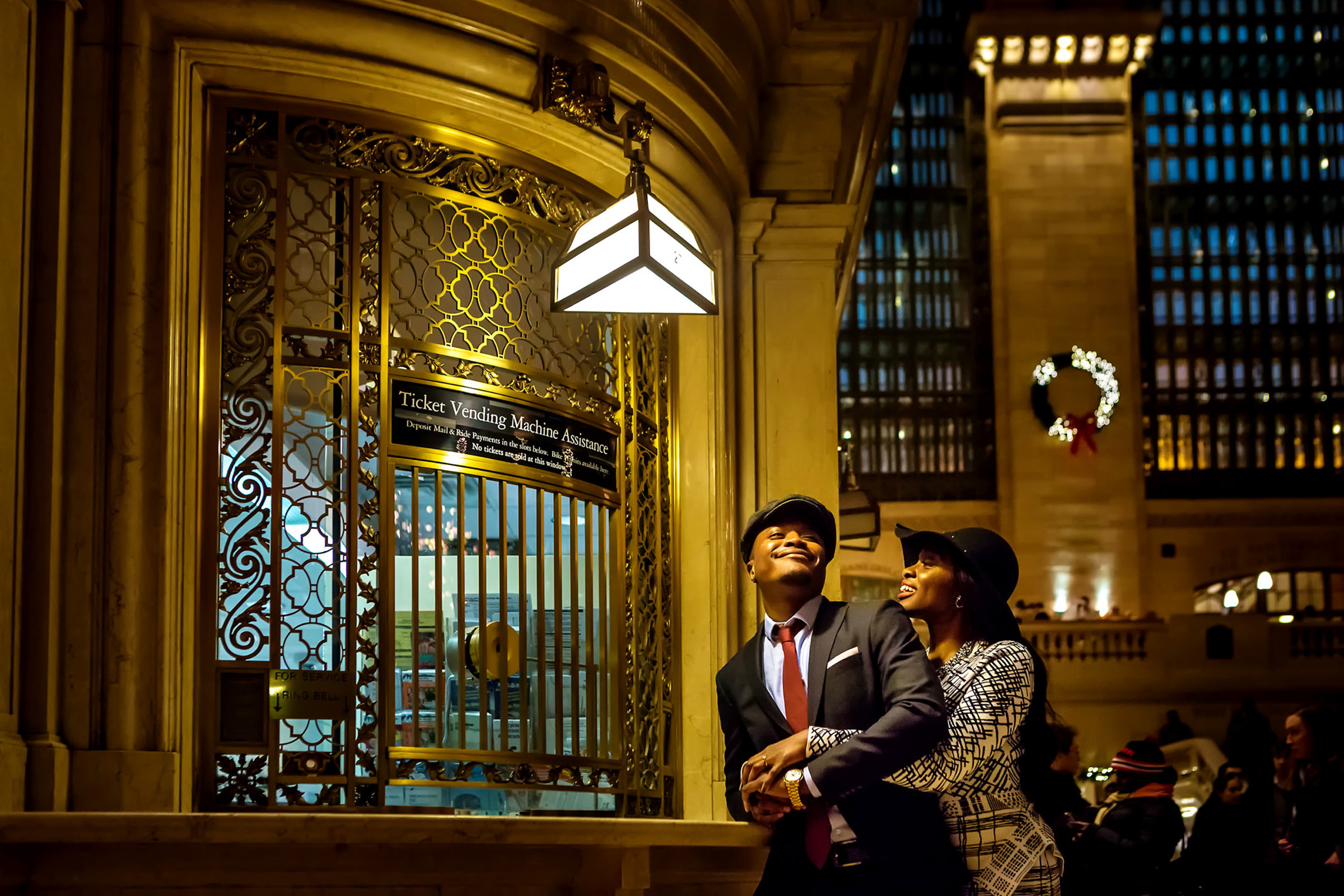Couple leaning against ticket counter at Grand Central Station - photo by Alakija Studios