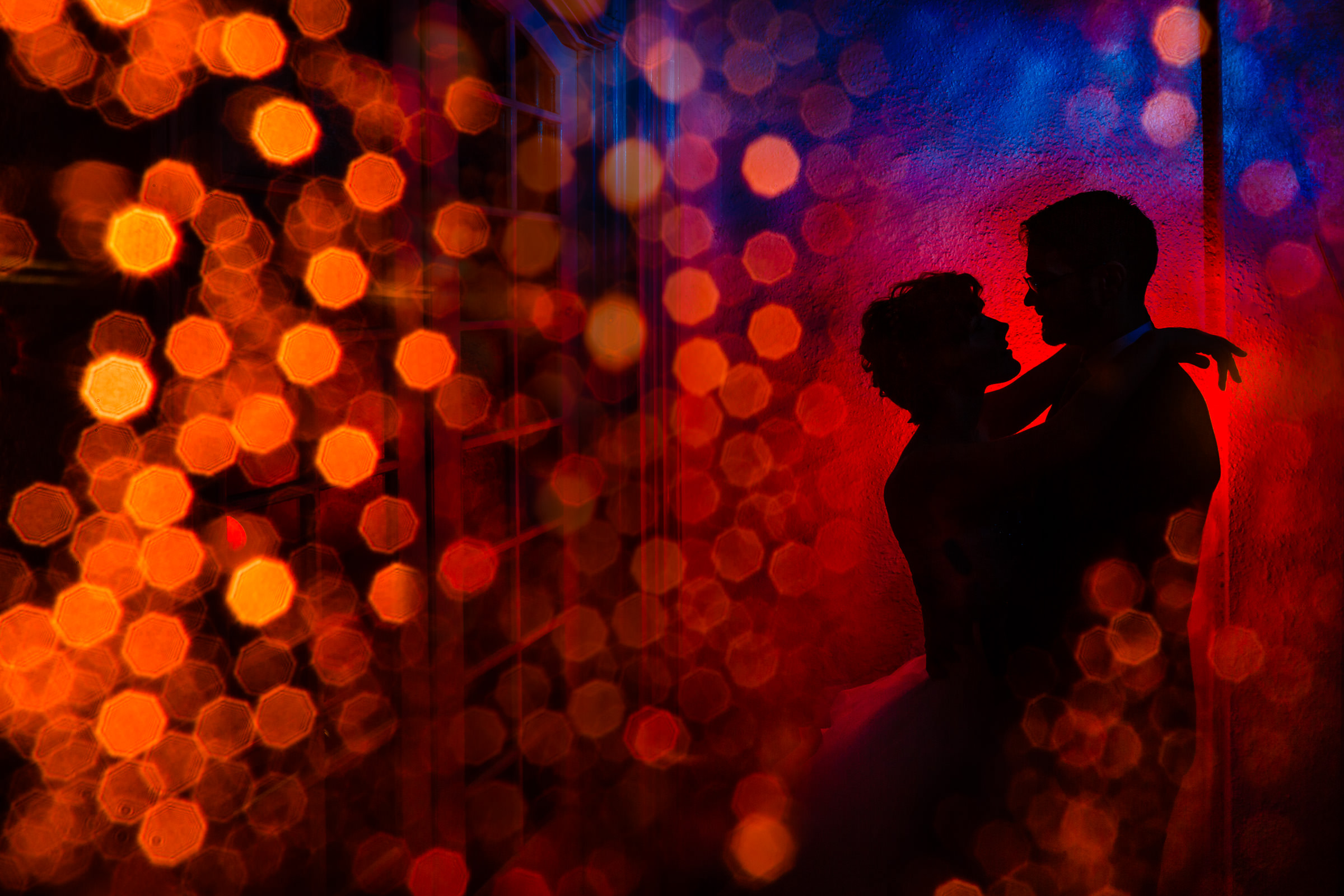 Silhouette of couple embracing with bokeh effects - photo by JOS & TREE