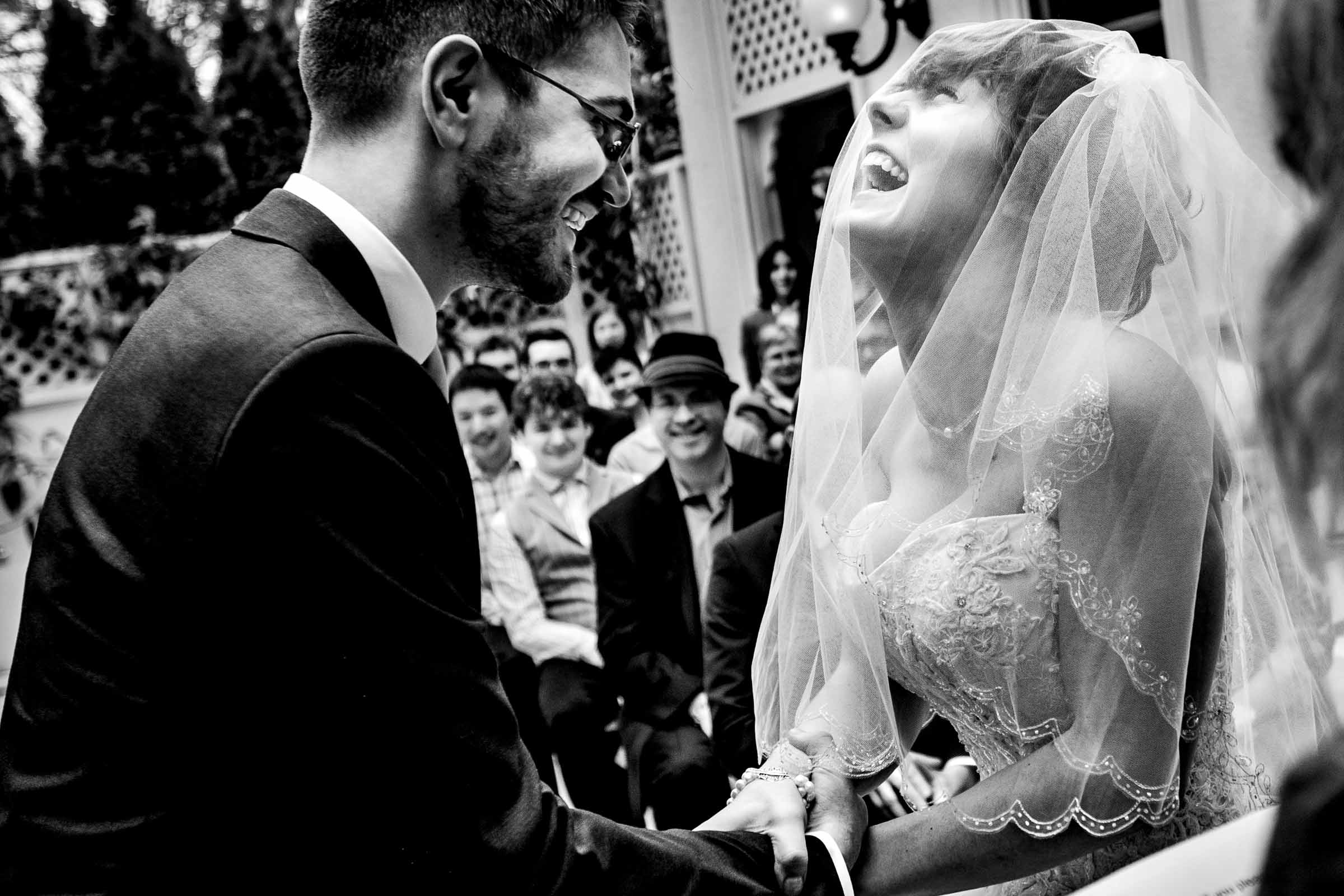 Bride and groom laughing during ceremony - photo by JOS & TREE
