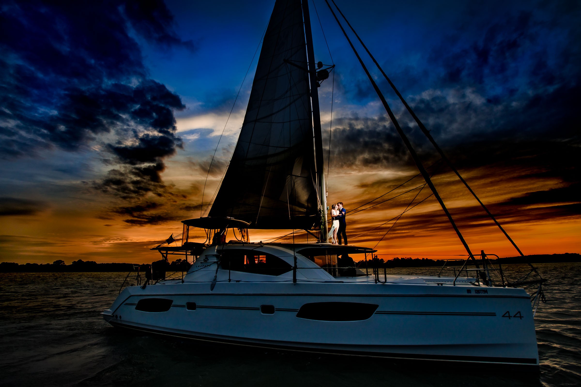 Couple on catamaran at sunset - photo by JOS & TREE