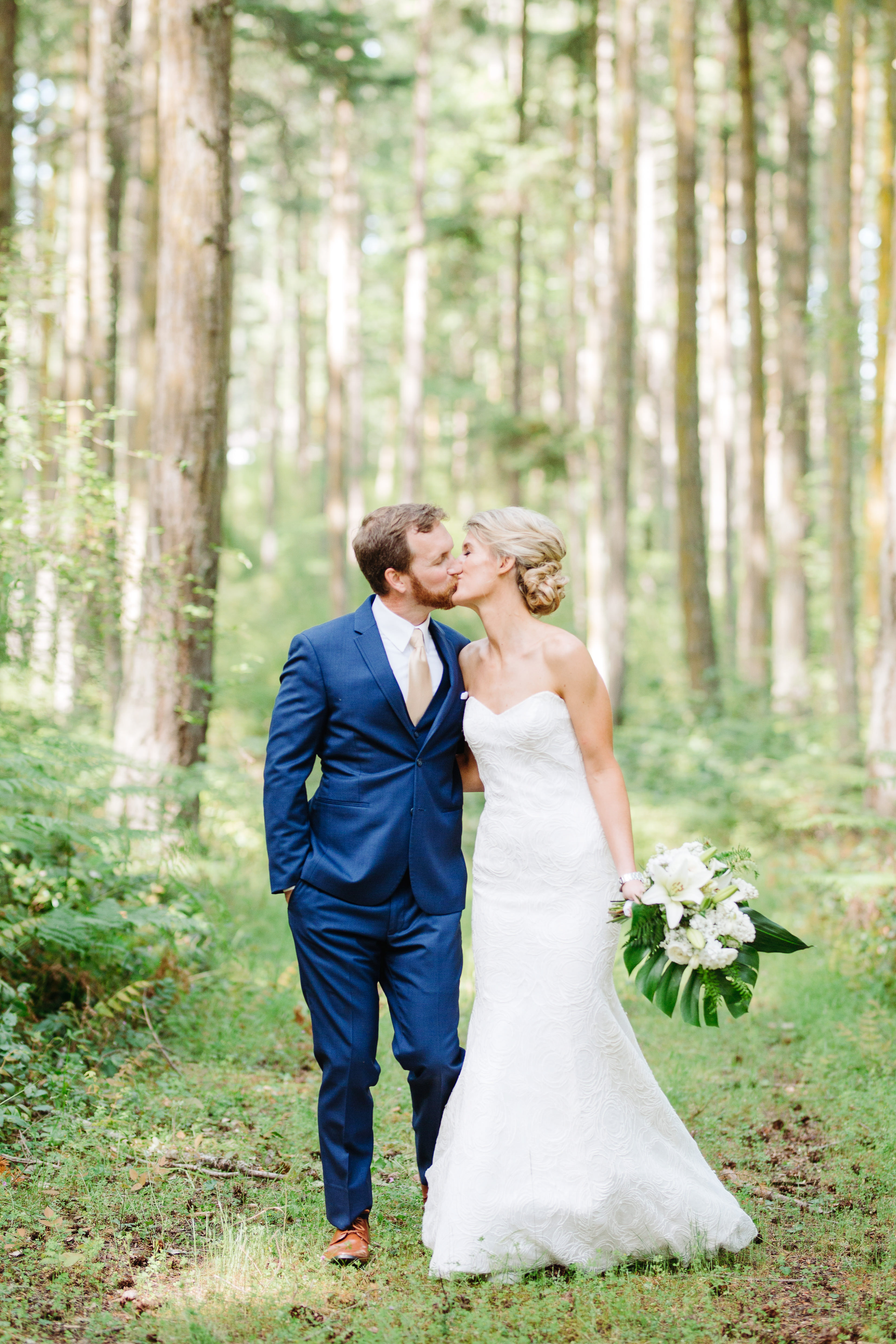 Bride and groom kiss in forest - photo by Cameron Zegers Photography