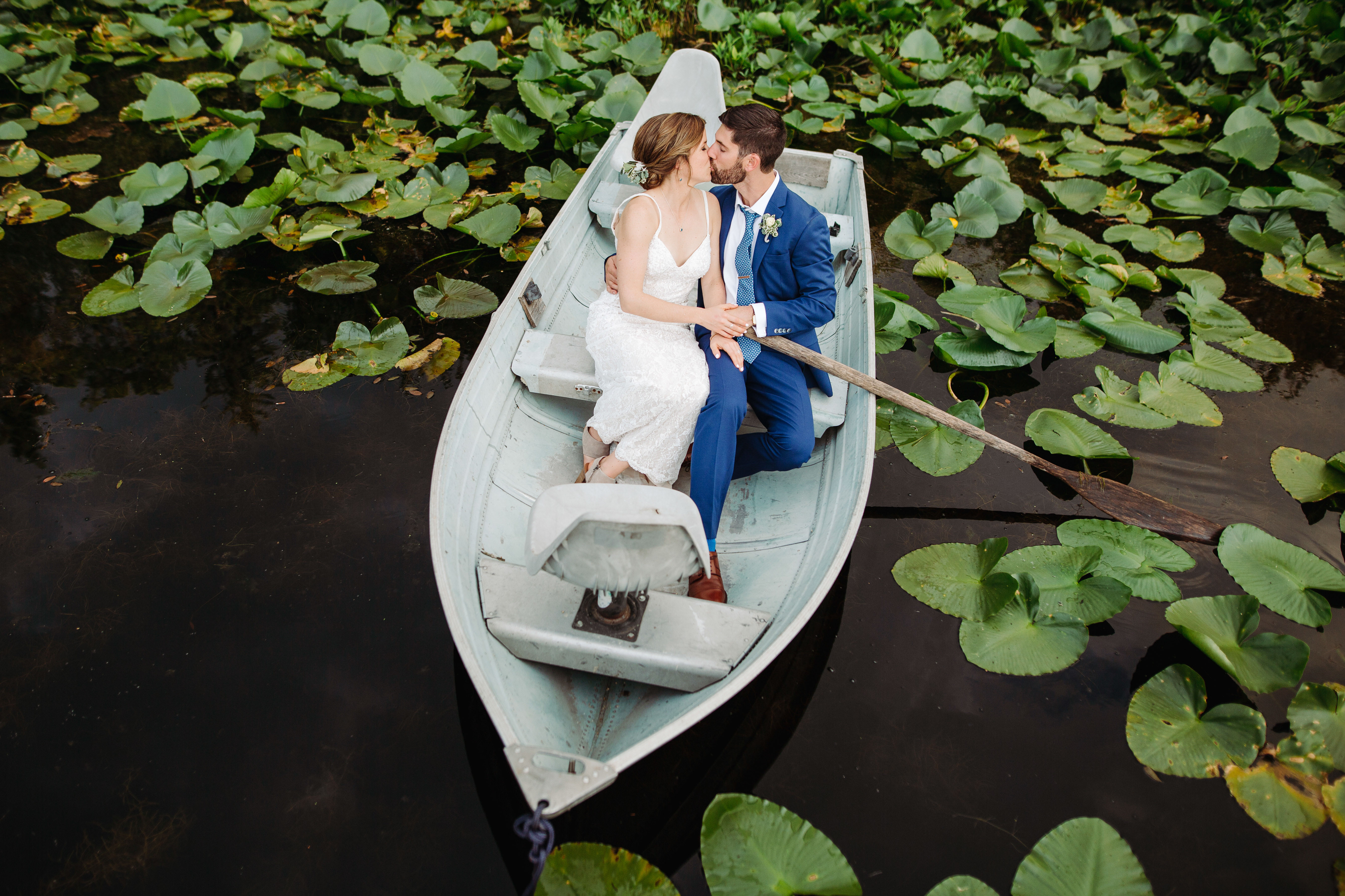 Bride and groom kissing in rowboat amongst lily pads - photo by Cameron Zegers Photography