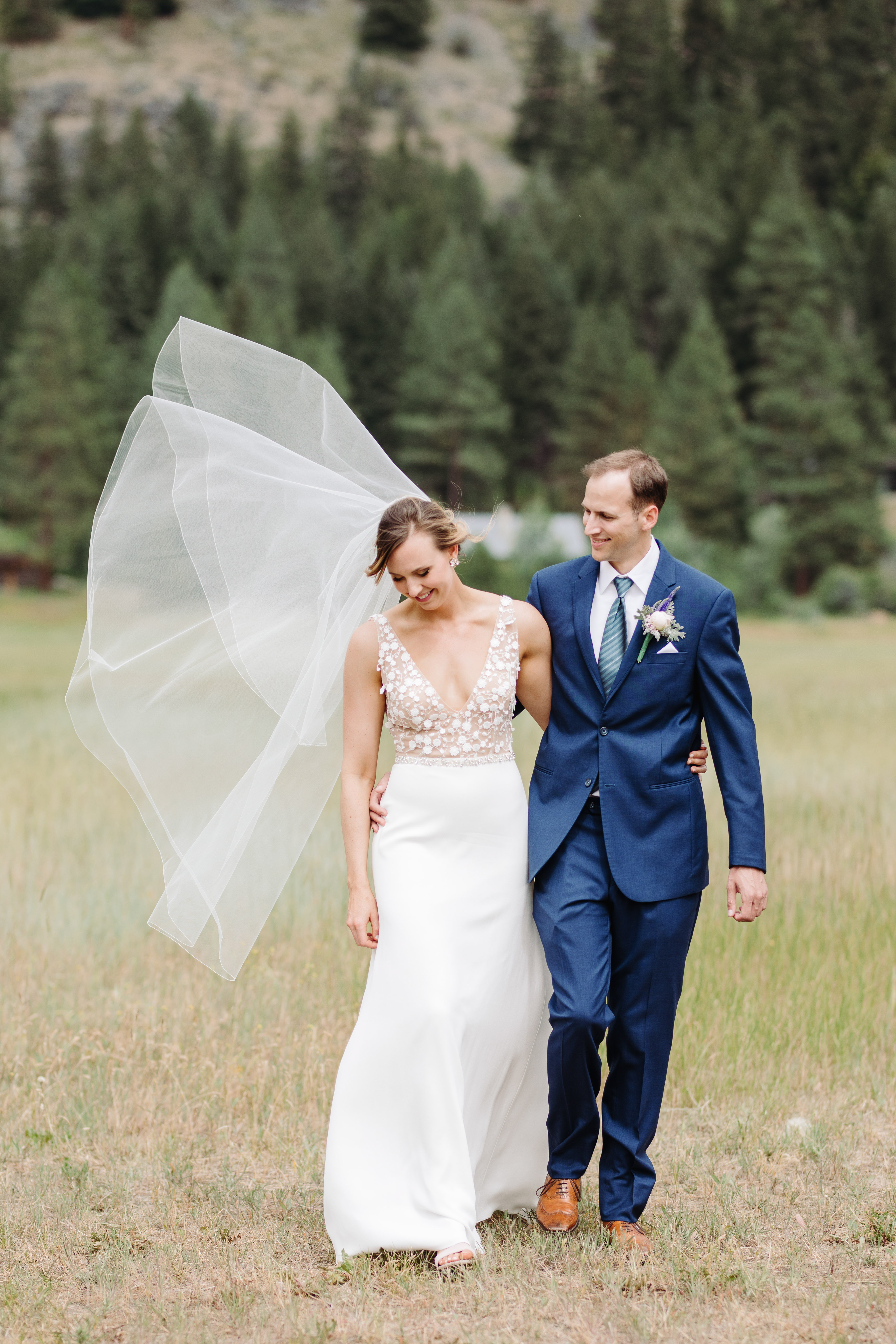 Bride and groom stroll through fields - photo by Cameron Zegers Photography