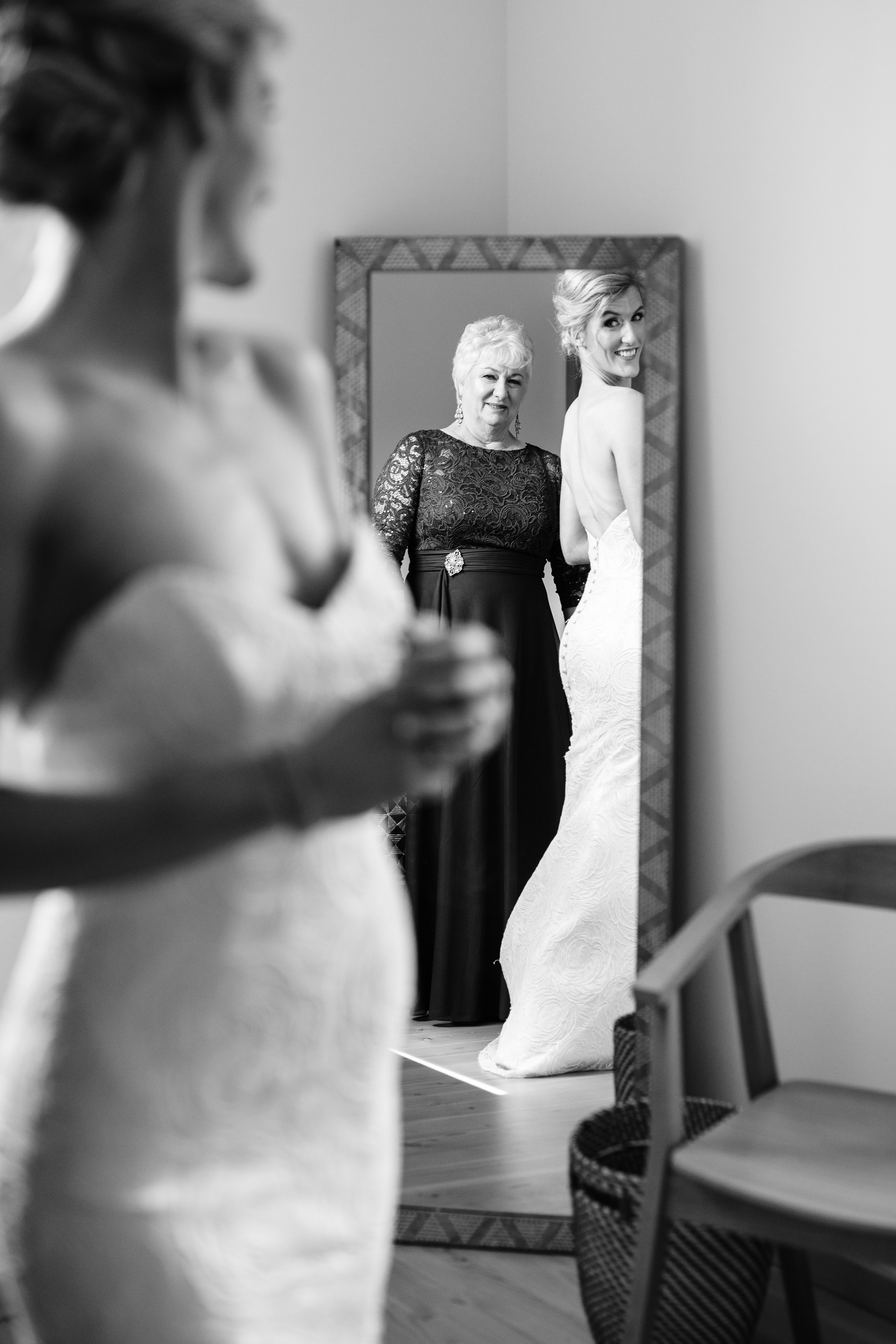 Bride and mom admiring wedding gown in mirror - photo by Cameron Zegers Photography