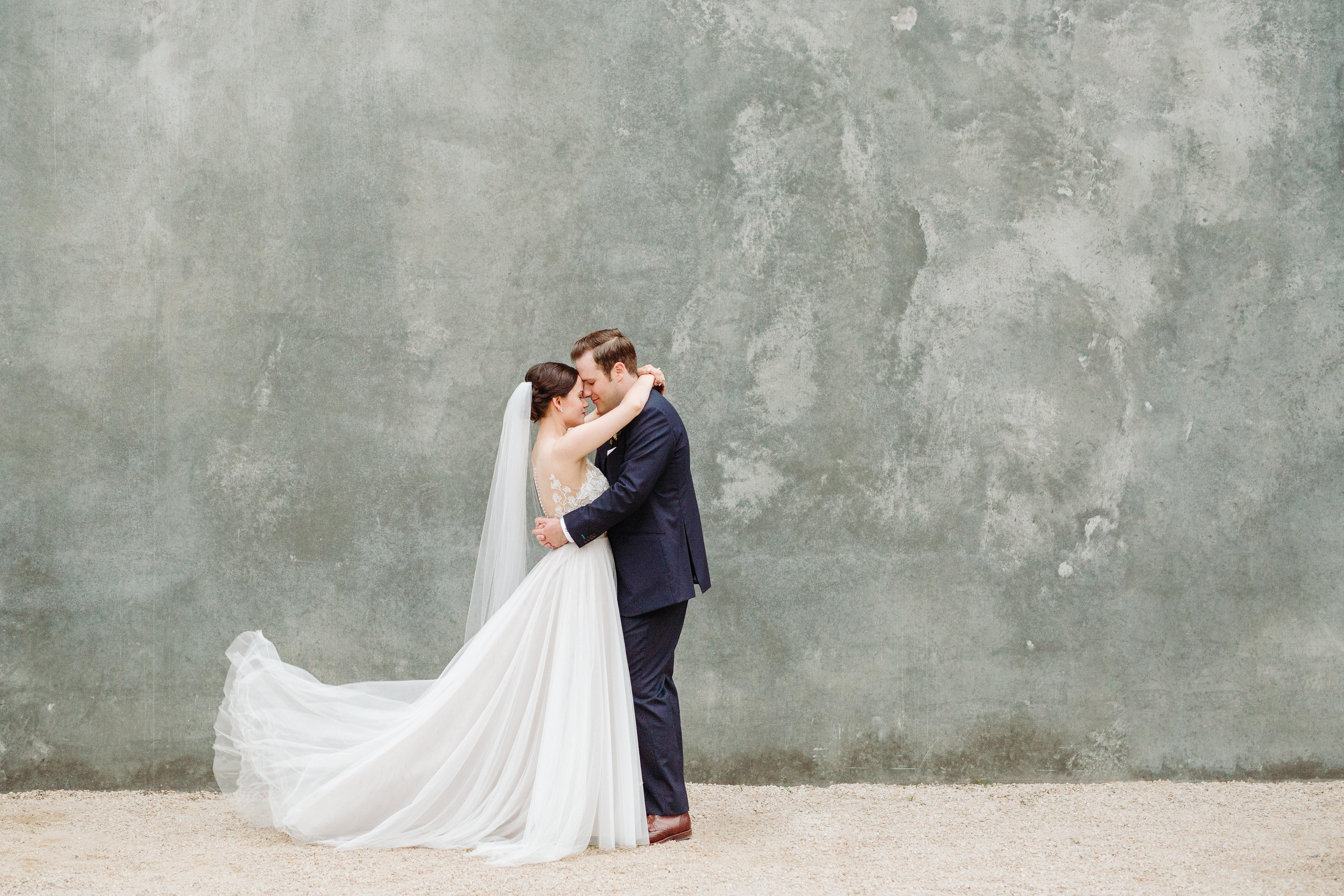 Bride and groom portrait against cement wall - photo by Cameron Zegers Photography