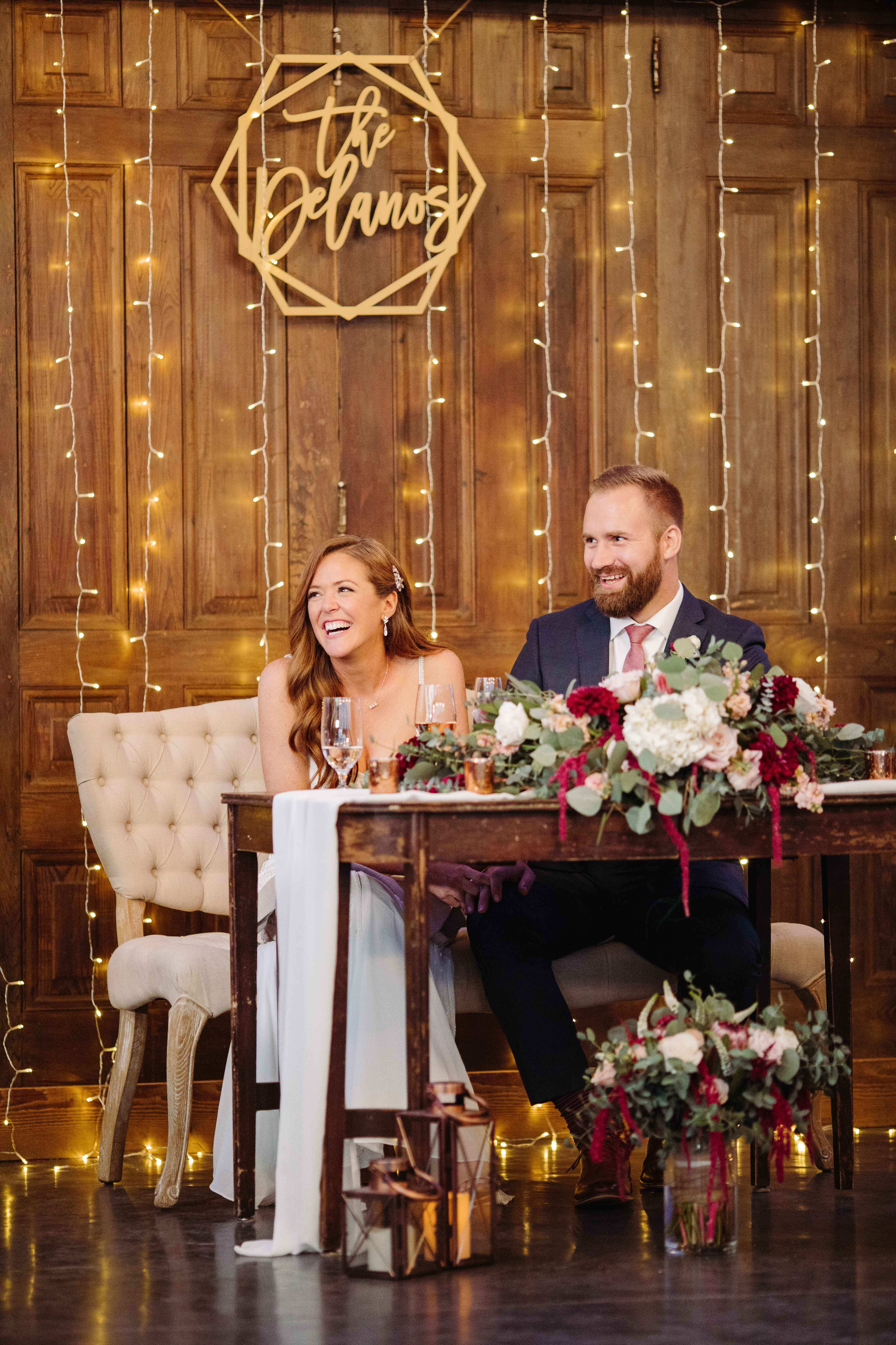 Couple at wedding table with love lies bleeding centerpieces - photo by Cameron Zegers Photography