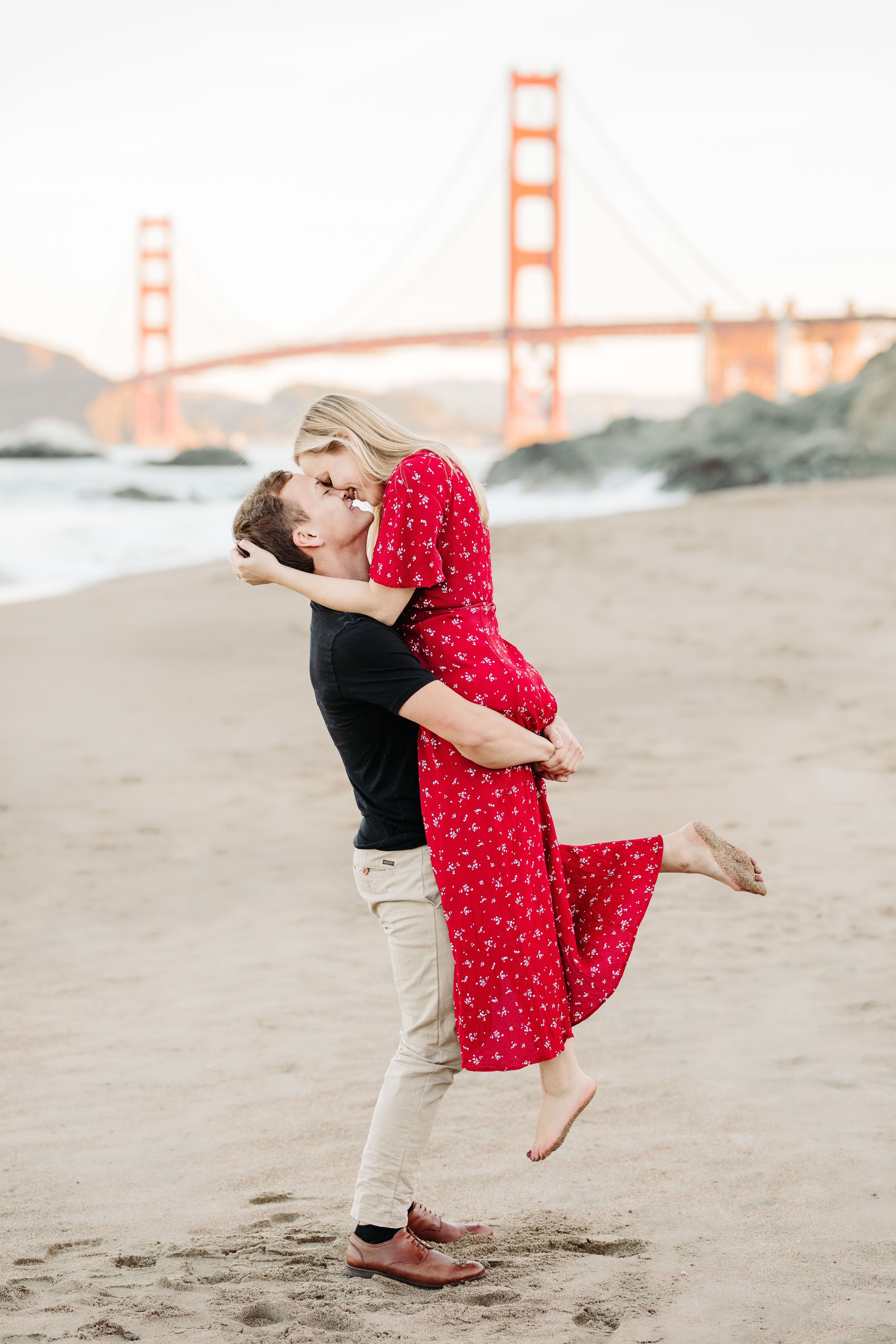 Engagement portrait of couple kissing against San Francisco bridge - photo by Cameron Zegers Photography