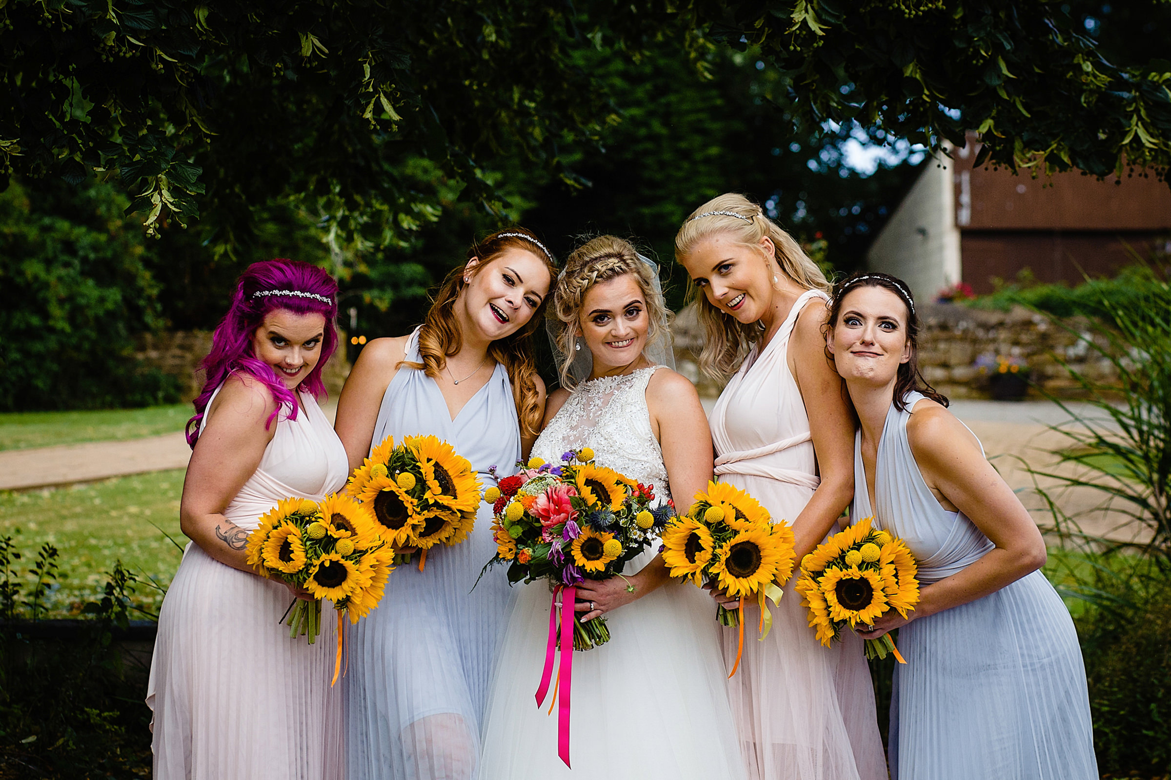 Bridal party with sunflower bouquets making faces for the camera - photo by Emma + Rich