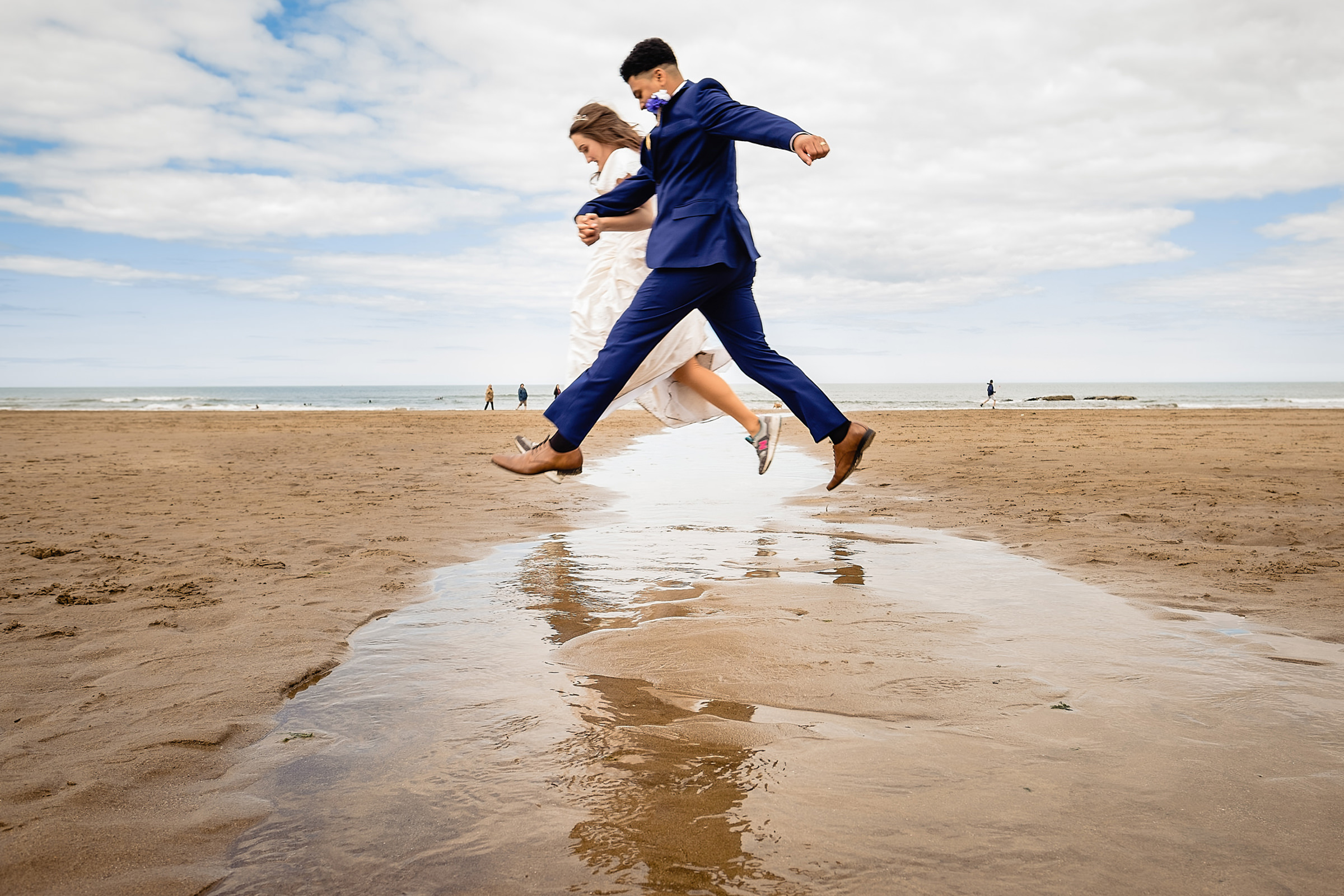 Bride and groom jump across water at the beach - photo by Emma + Rich