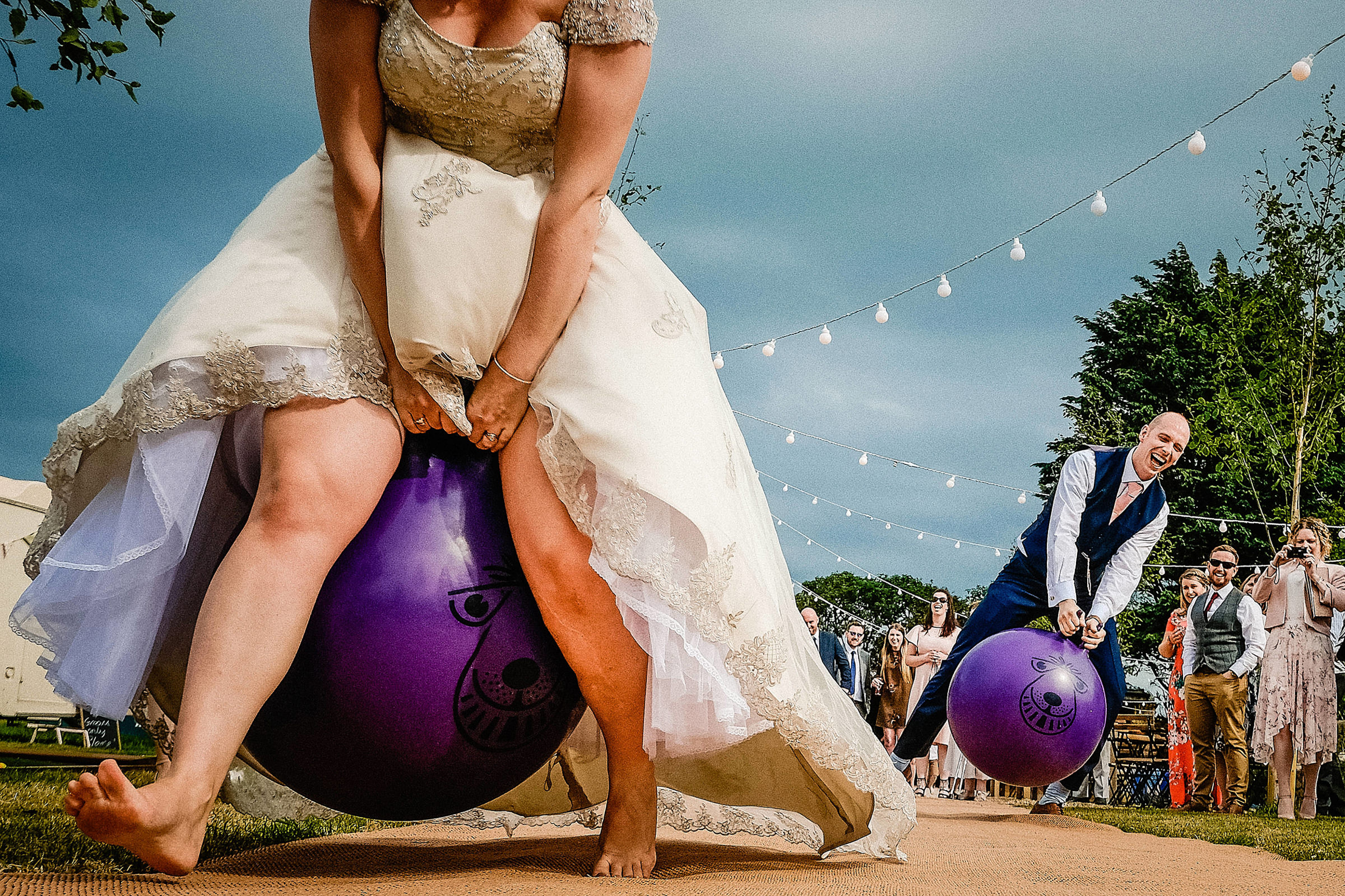 Bride and groom on purple bouncy balls - photo by Emma + Rich