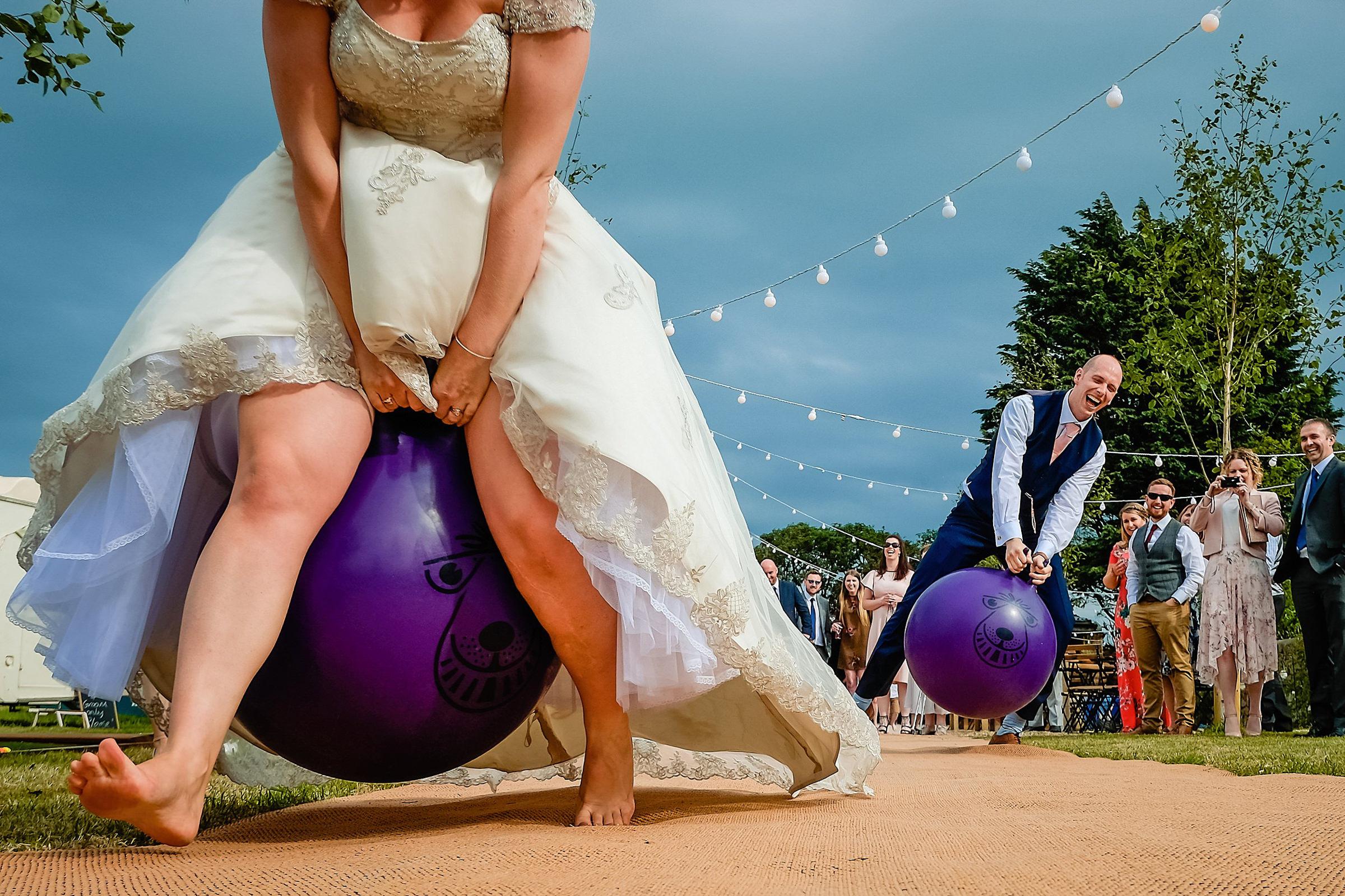 Bride and groom riding purple hop along balls - photo by Emma + Rich - England