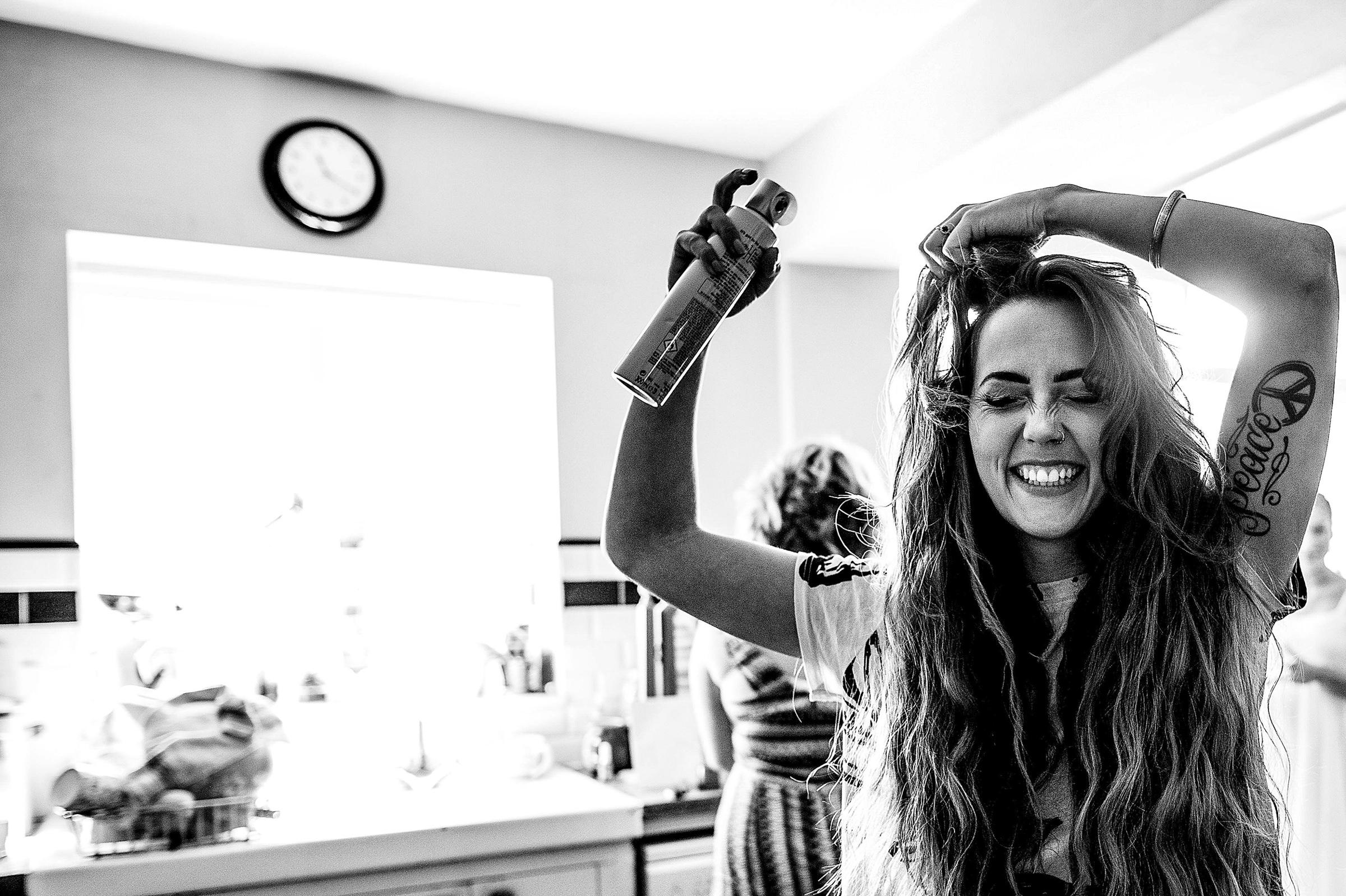 Bride applying hairspray - photo by Emma + Rich