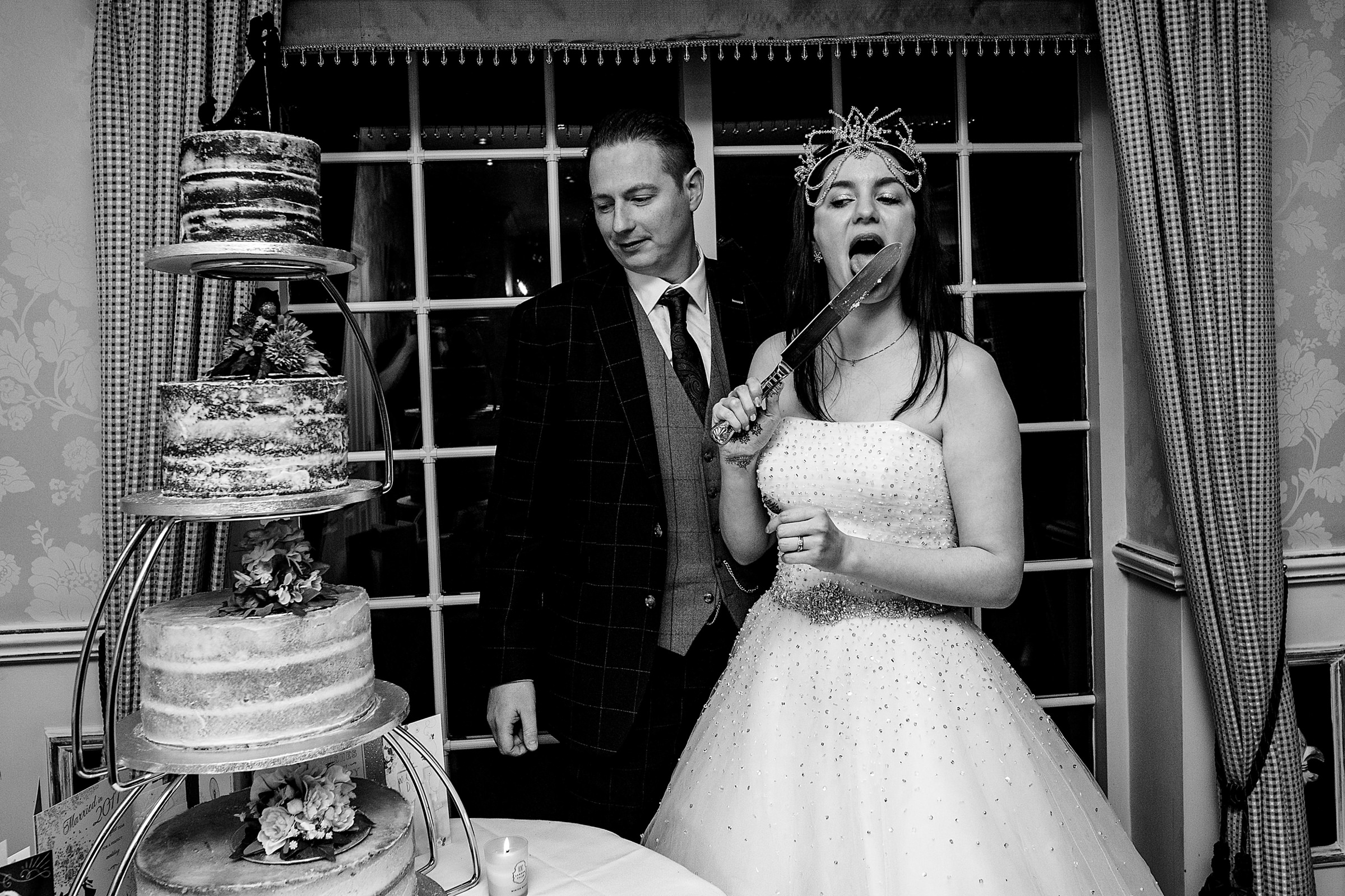 Bride licks the cake knife - photo by Emma + Rich