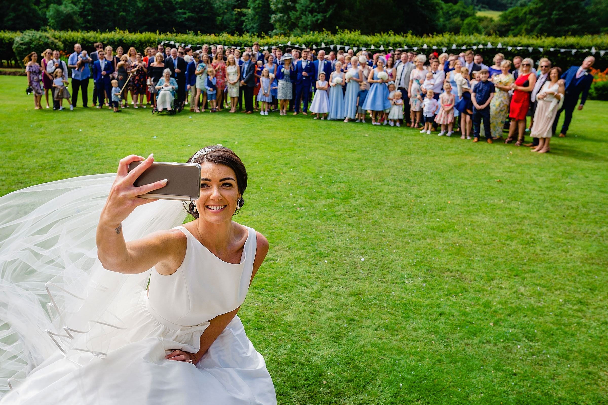 Bride taking selfie with group shot - photo by Emma + Rich