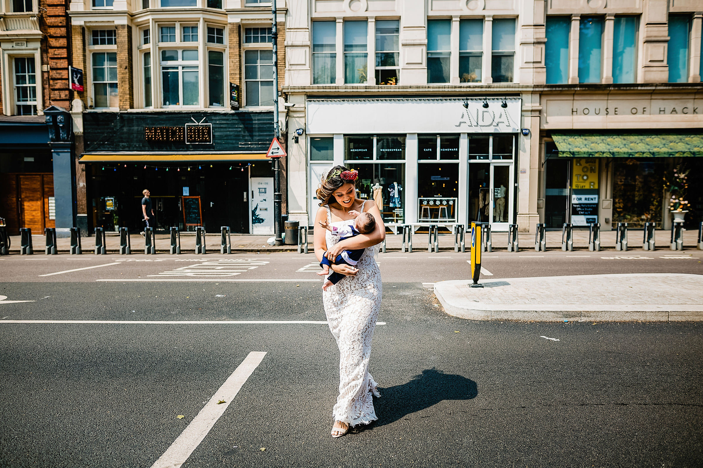 Bride with baby in arms crossing street - photo by Emma + Rich