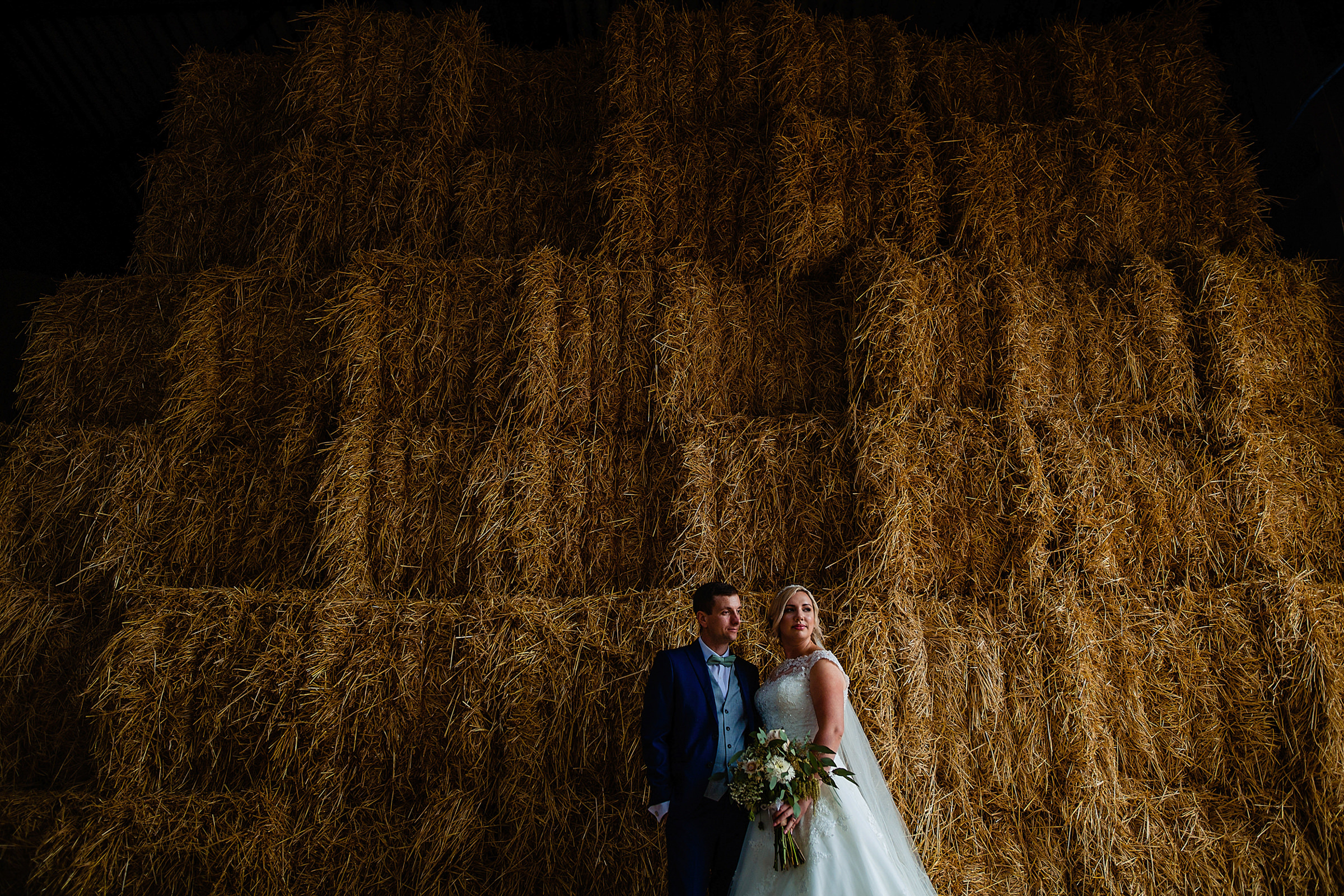 Couple against huge stack of hay bales - photo by Emma + Rich