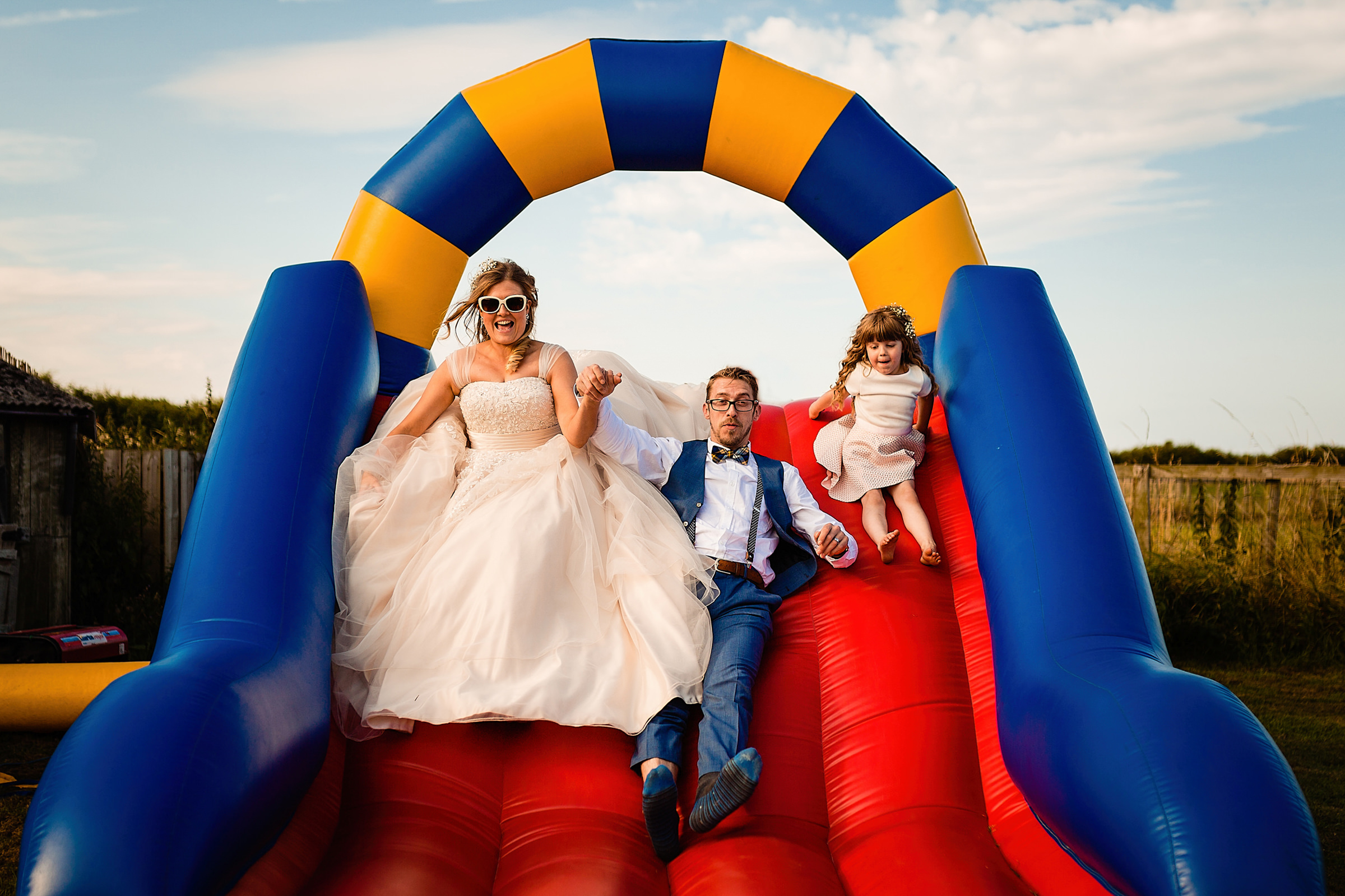 Couple and girl on inflatable slide - photo by Emma + Rich