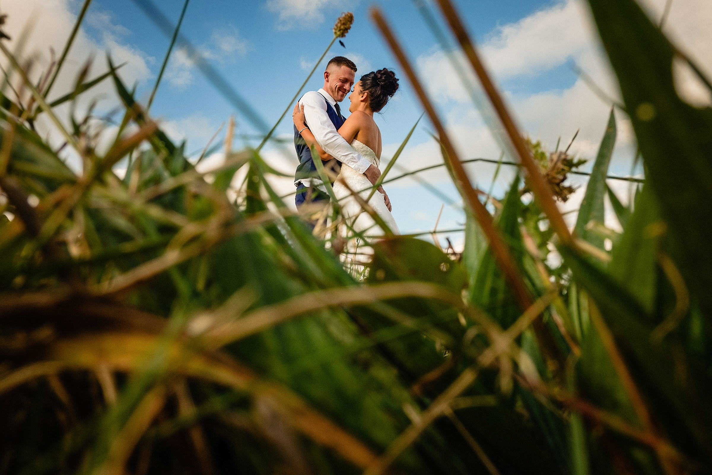 Couple embrace seen through grasses - photo by Emma + Rich