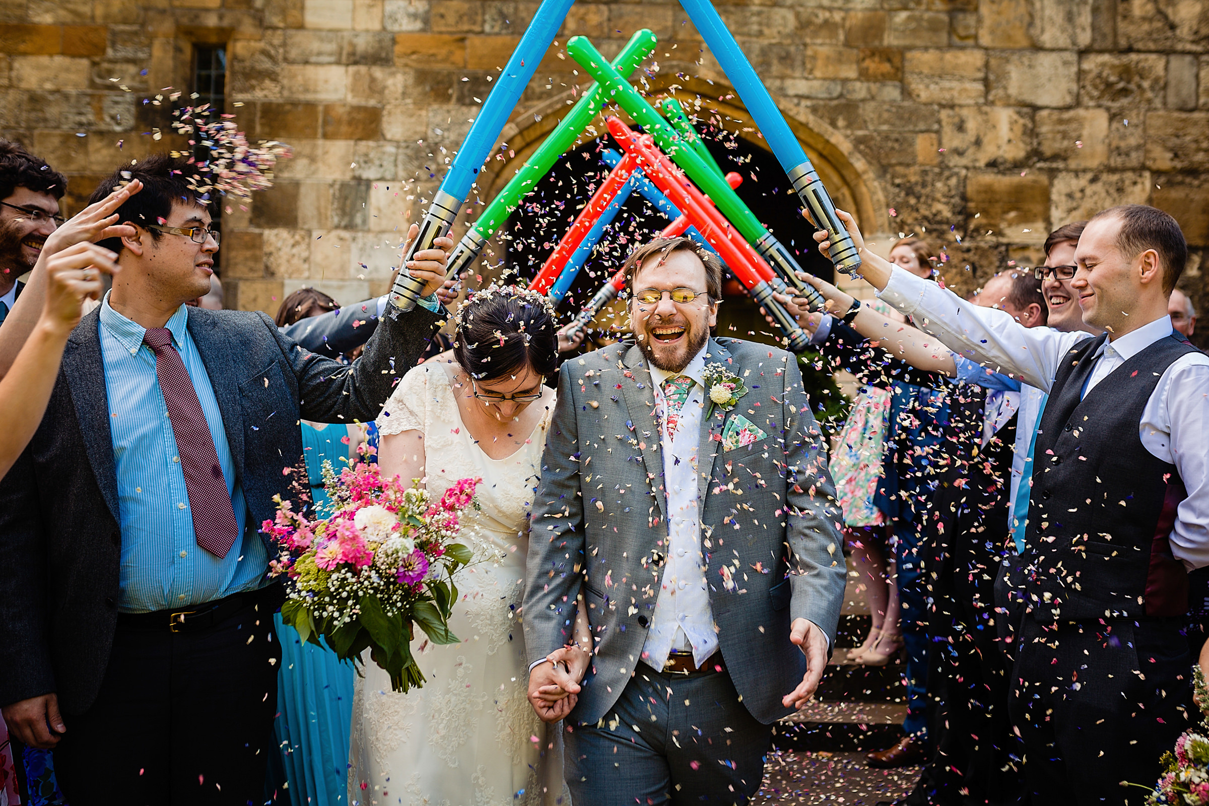 Couple exits church under arch of light sabers - photo by Emma + Rich