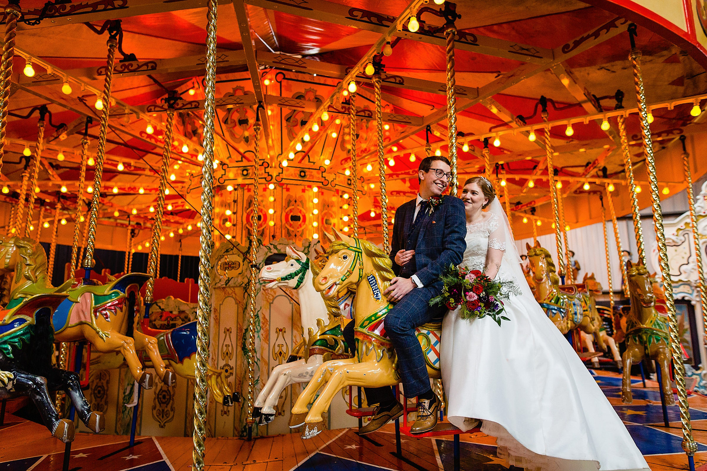 Couple on colorful carousel - photo by Emma + Rich