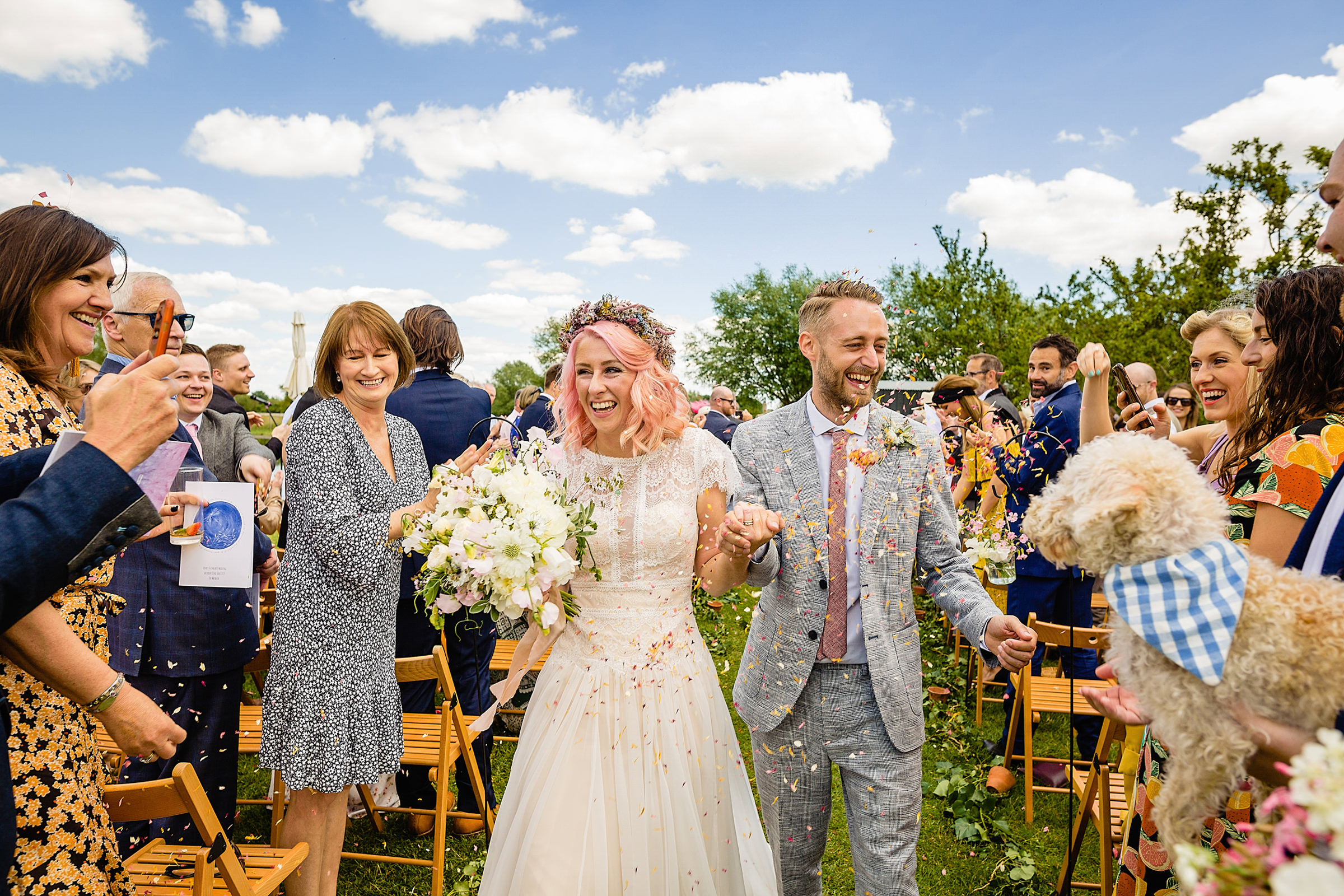 Couple outdoor recessional under confetti shower - photo by Emma + Rich