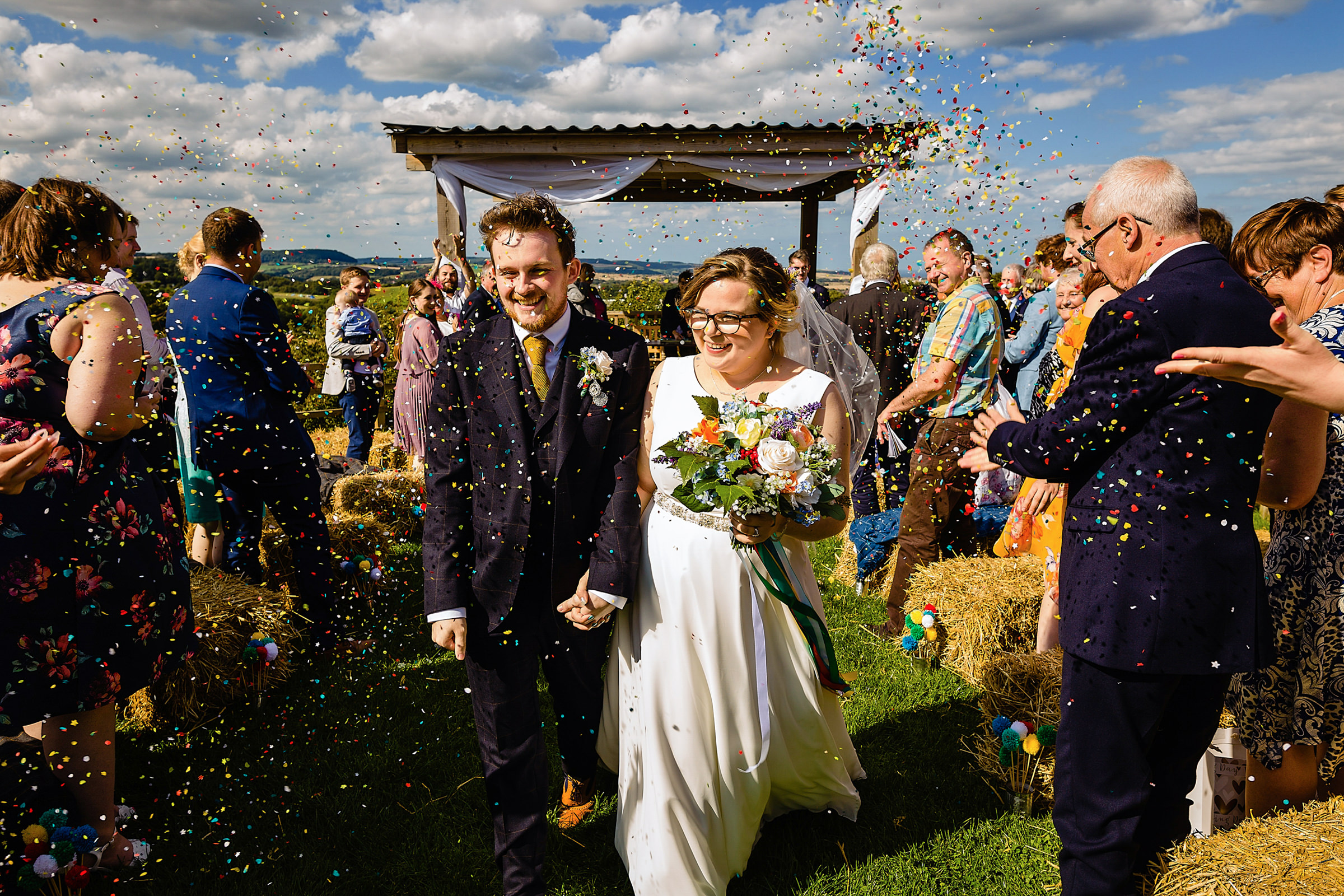 Couple recessional under confetti - photo by Emma + Rich