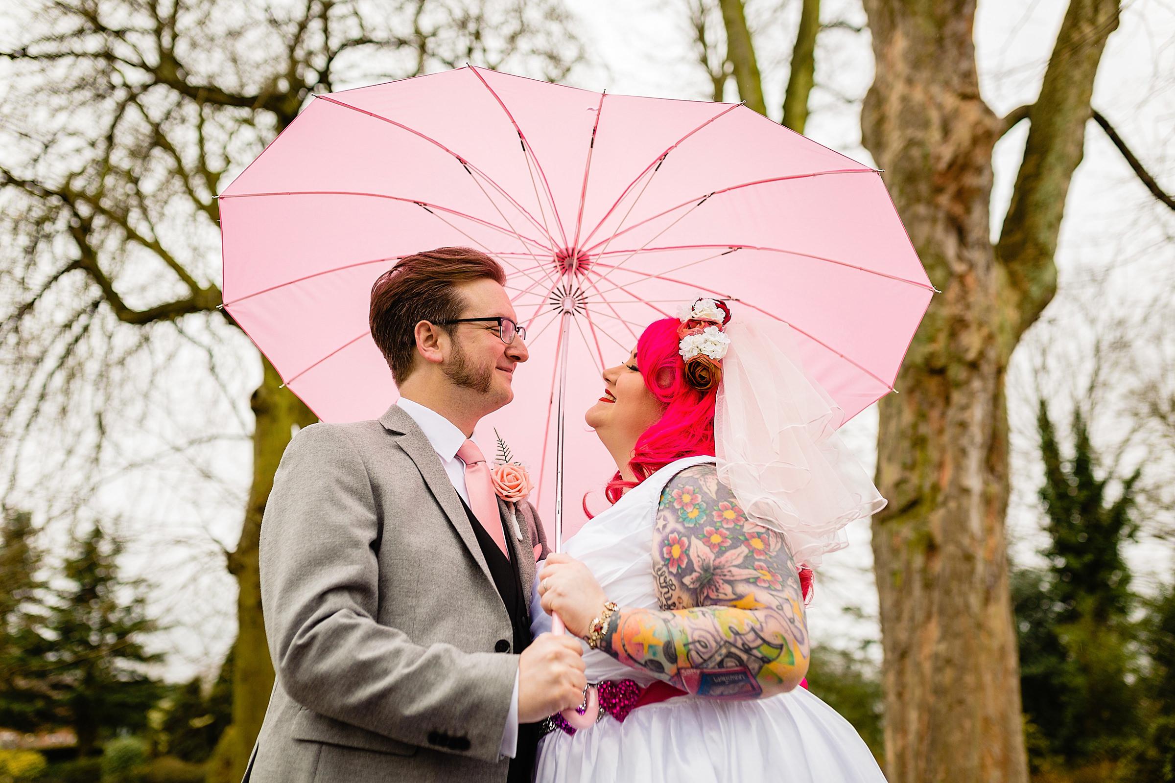 Couple under pink umbrella - photo by Emma + Rich