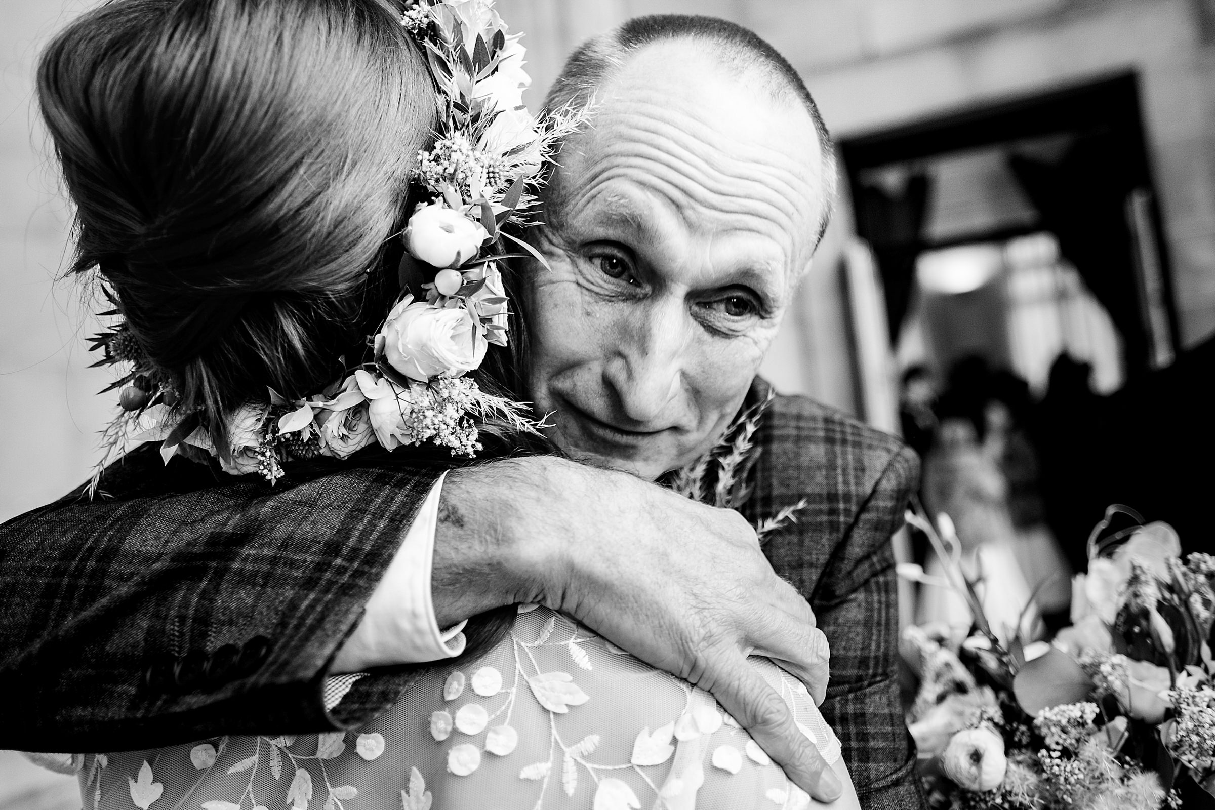 Groom in plaid suit hugs his bride wearing floral wreath - photo by Emma + Rich
