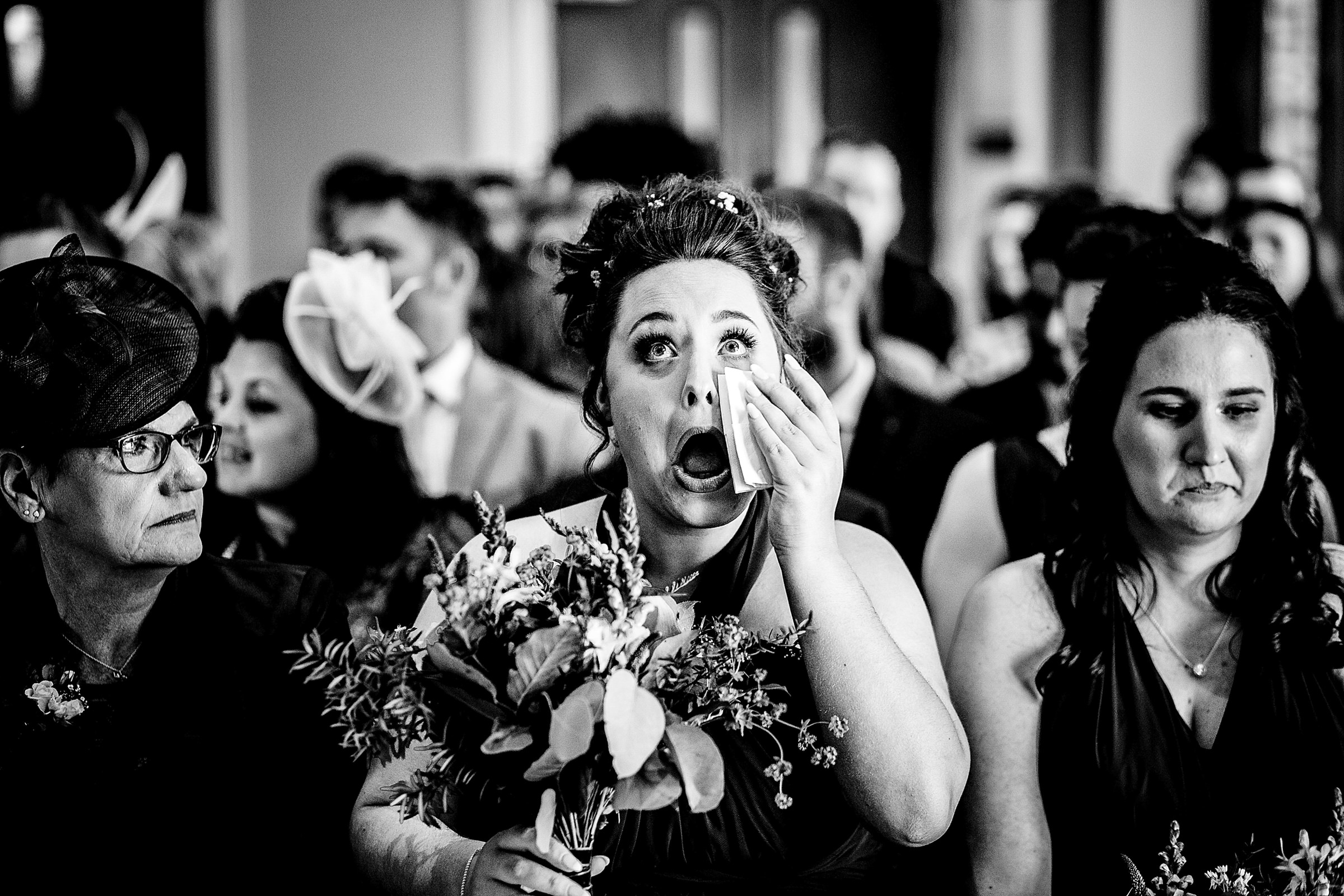 Hilarious photo of bridesmaid getting disapproving look while wiping tear- photo by Emma + Rich
