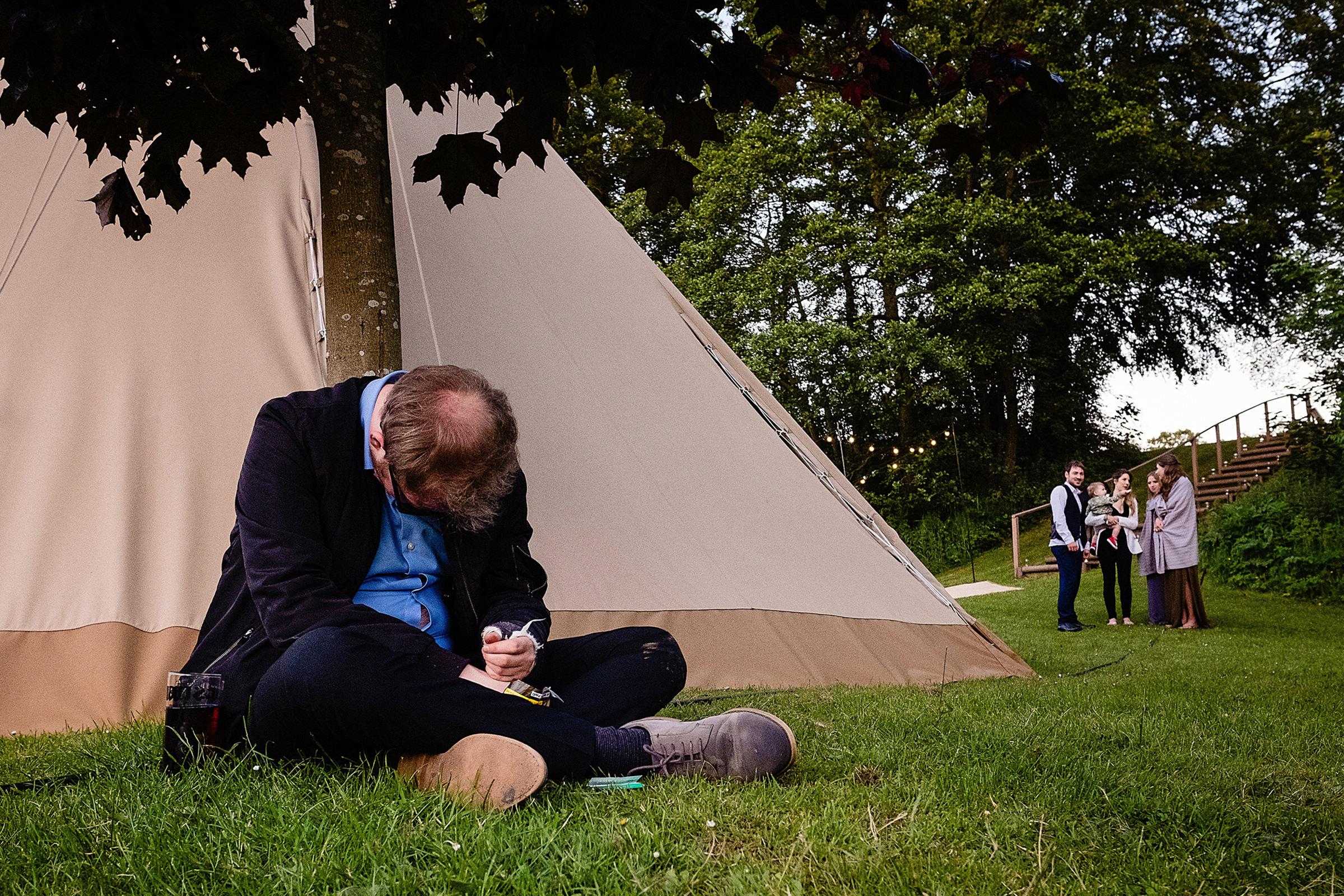 Man having a snooze outside tent - photo by Emma + Rich