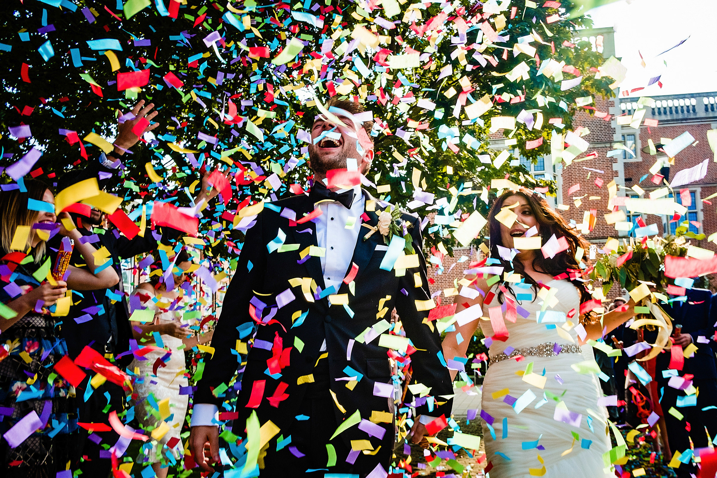 Rainstorm of confetti on couple - photo by Emma + Rich