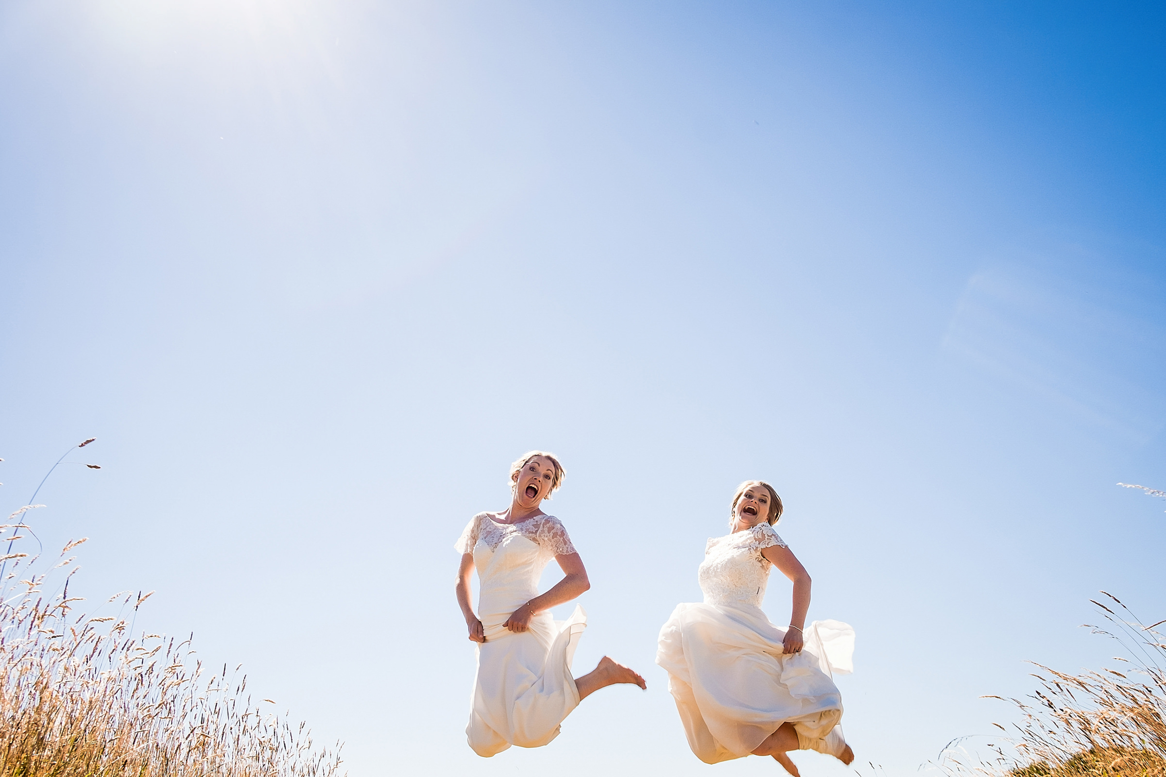 Two barefoot brides jumping - photo by Emma + Rich