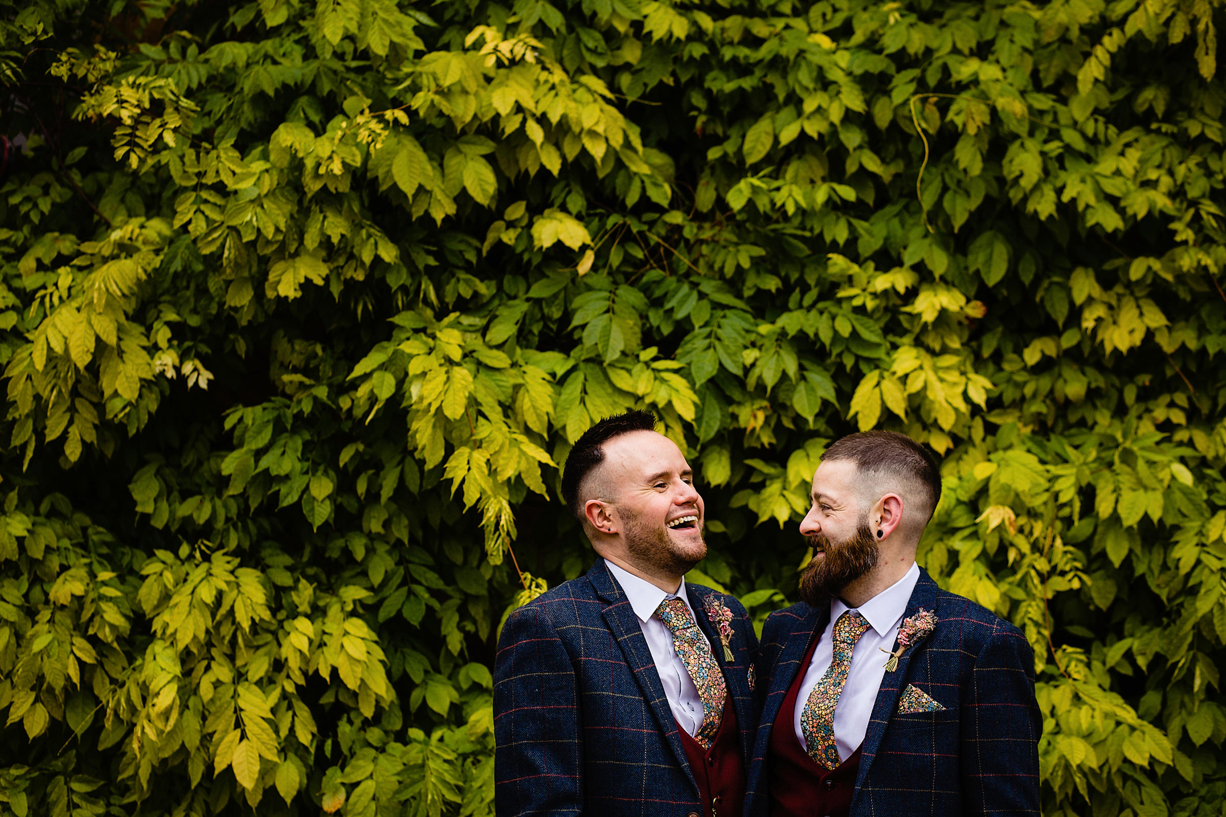 Two happy grooms wearing checked suits and floral ties - photo by Emma + Rich