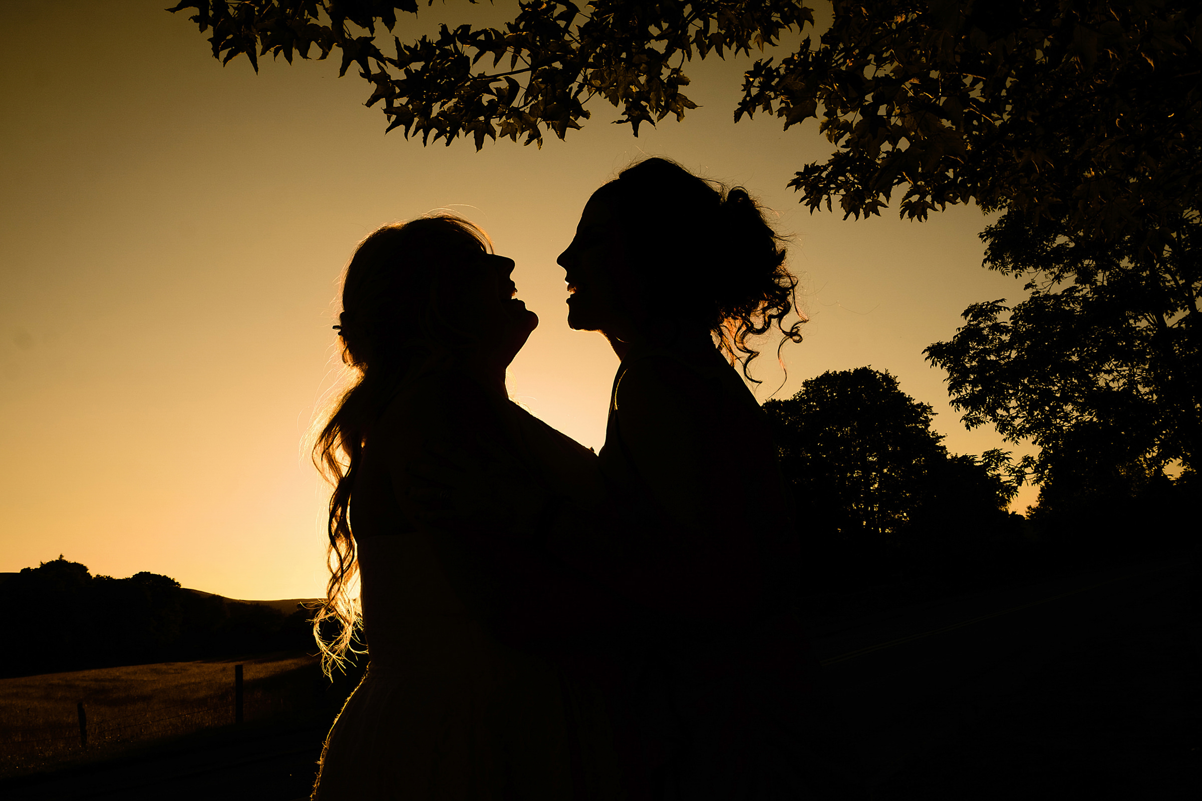 Warm silhouette of couple of brides under tree  - photo by Emma + Rich