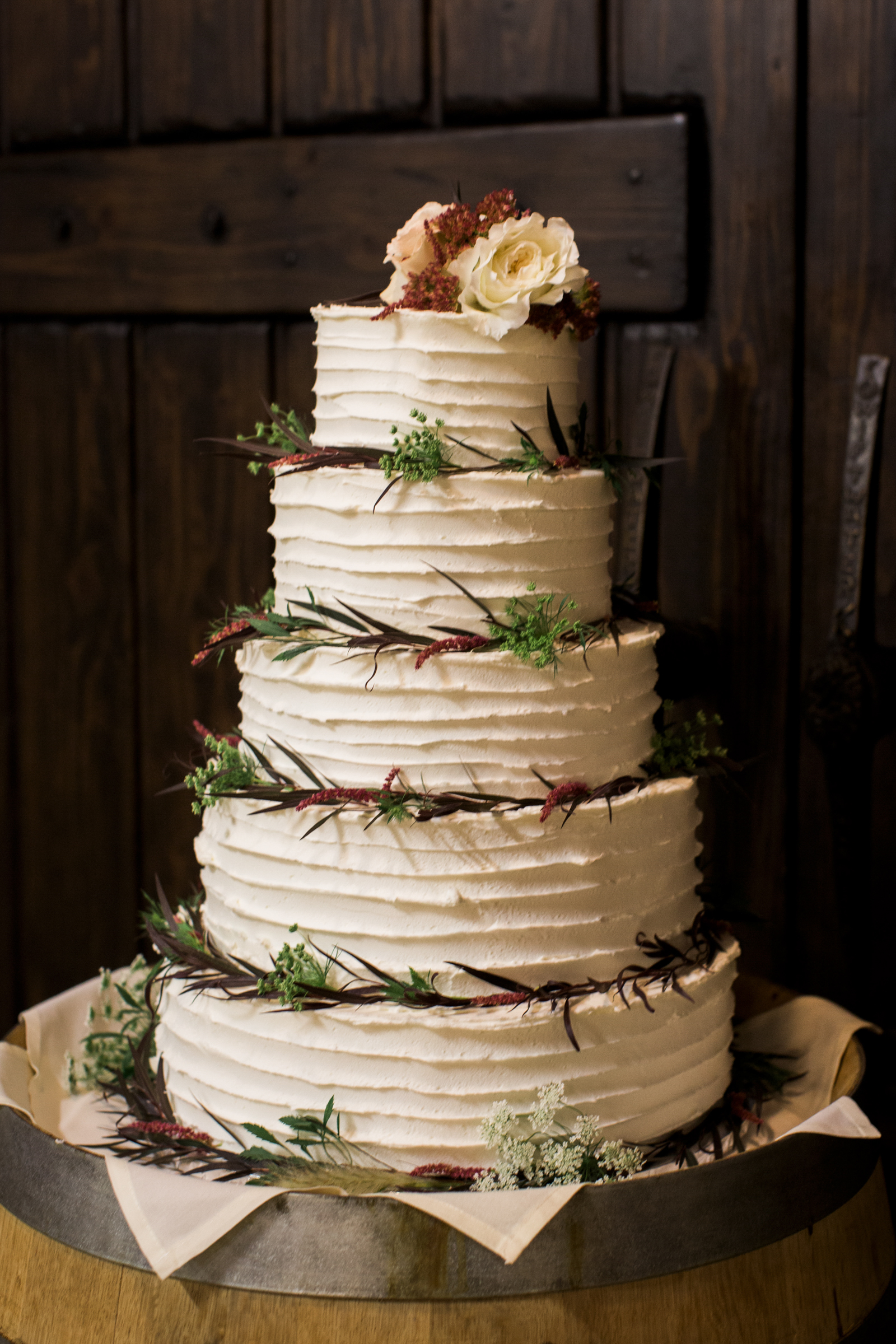 5-tier buttercream cake with greenery and roses - photo by Stephanie Cristalli Photography