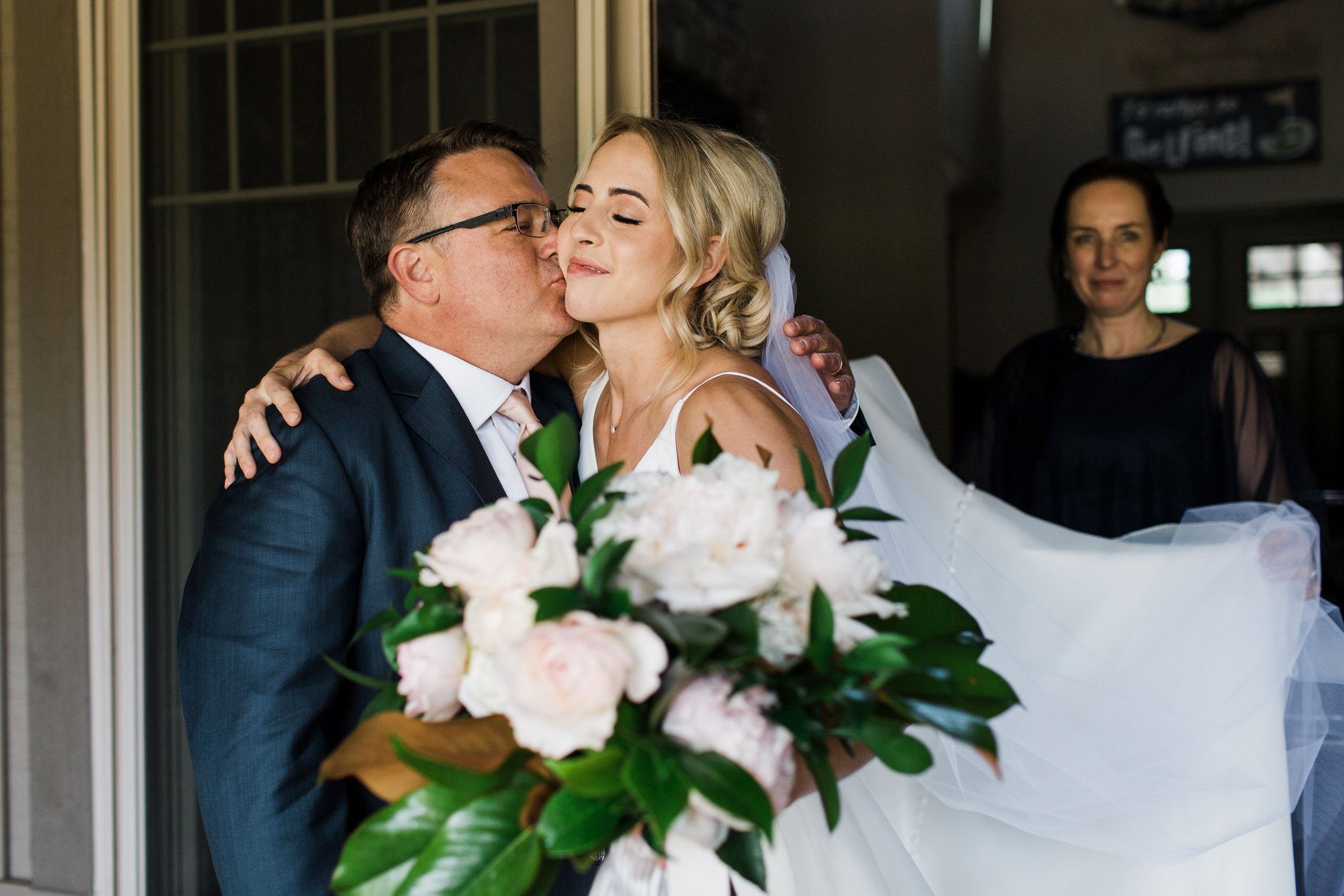 Bride embraces father while mom looks on - photo by Stephanie Cristalli Photography