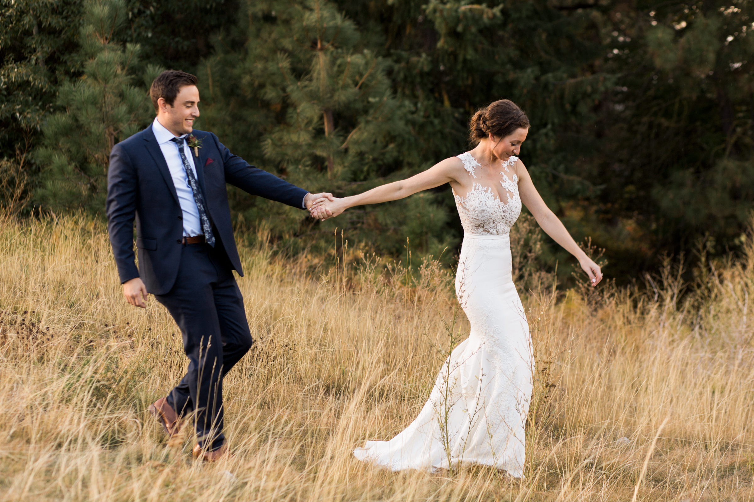 bride in applique lace dress with bustle pulls groom dow the hill - photo by Stephanie Cristalli Photography