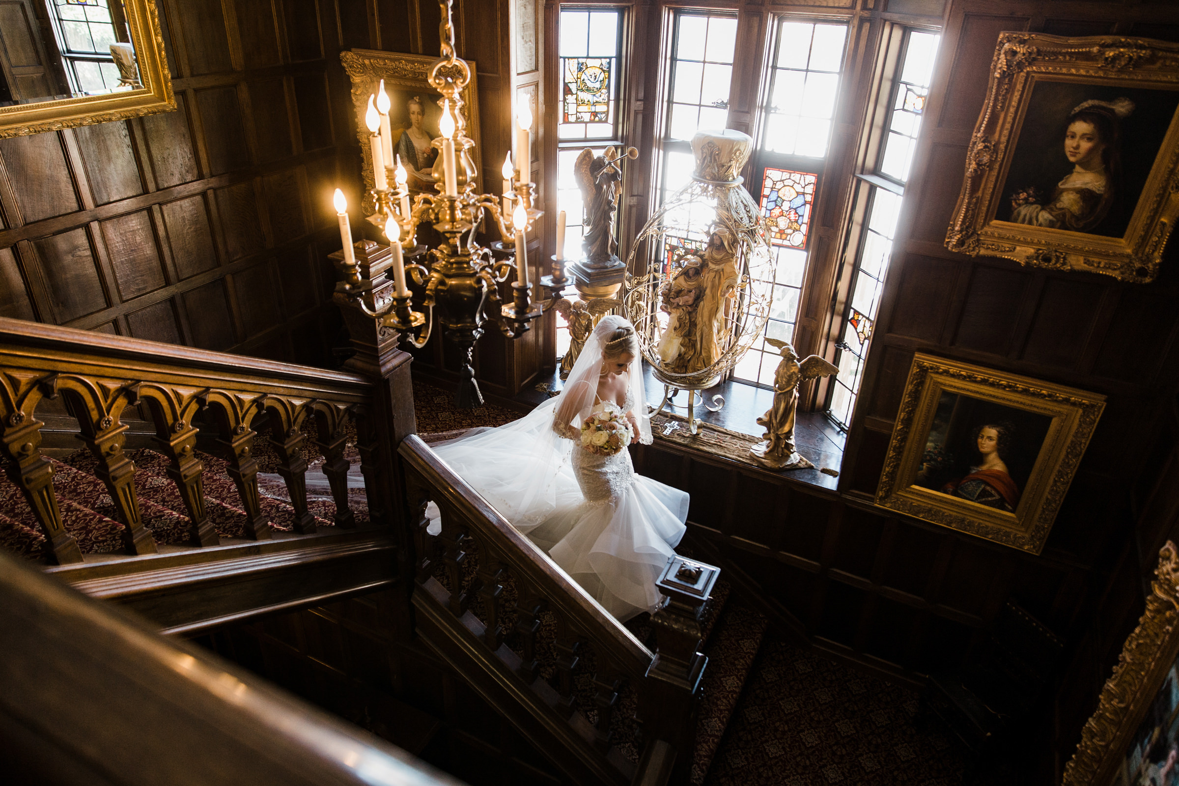 Bride in mermaid dress and long veil descends mansion stairway - photo by Stephanie Cristalli Photography