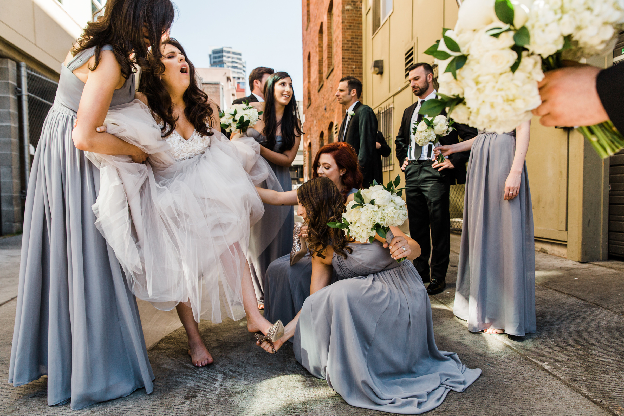Bride with aching feet has her shoes removed - photo by Stephanie Cristalli Photography